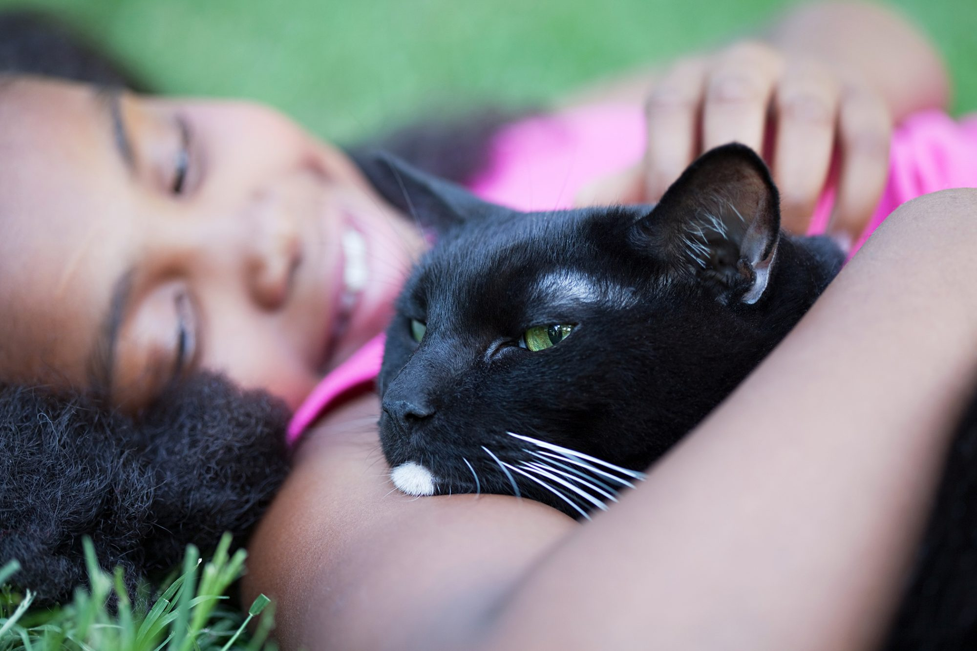 girl laying in grass with black cat