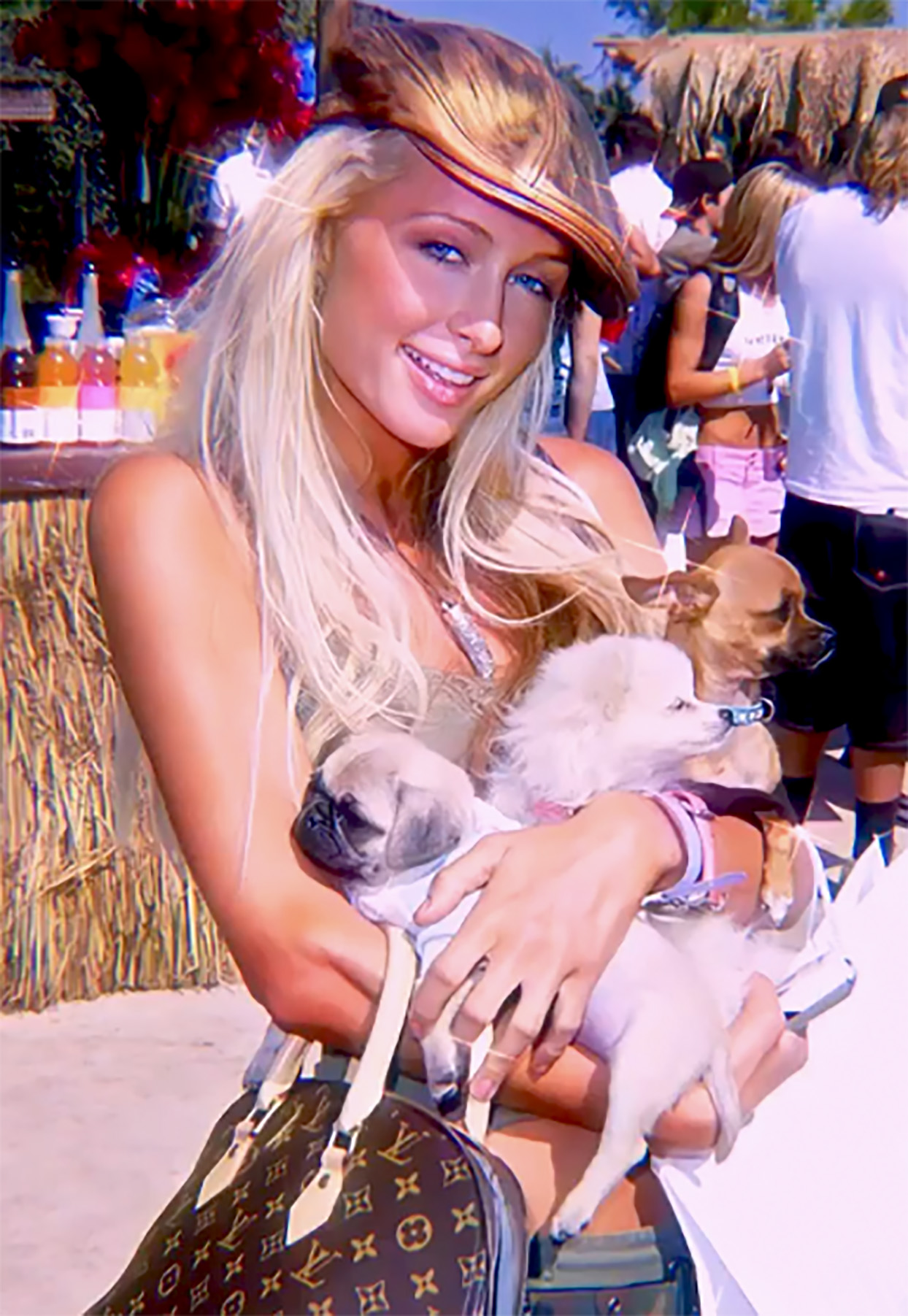 Photo of celebrity Paris Hilton holding three small dogs in her arms
