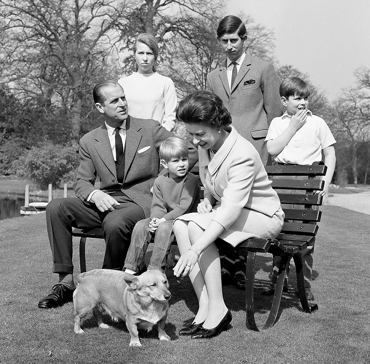 Family photo of Queen Elizabeth and Phillip, Elizabeth is leaning down to pet corgi