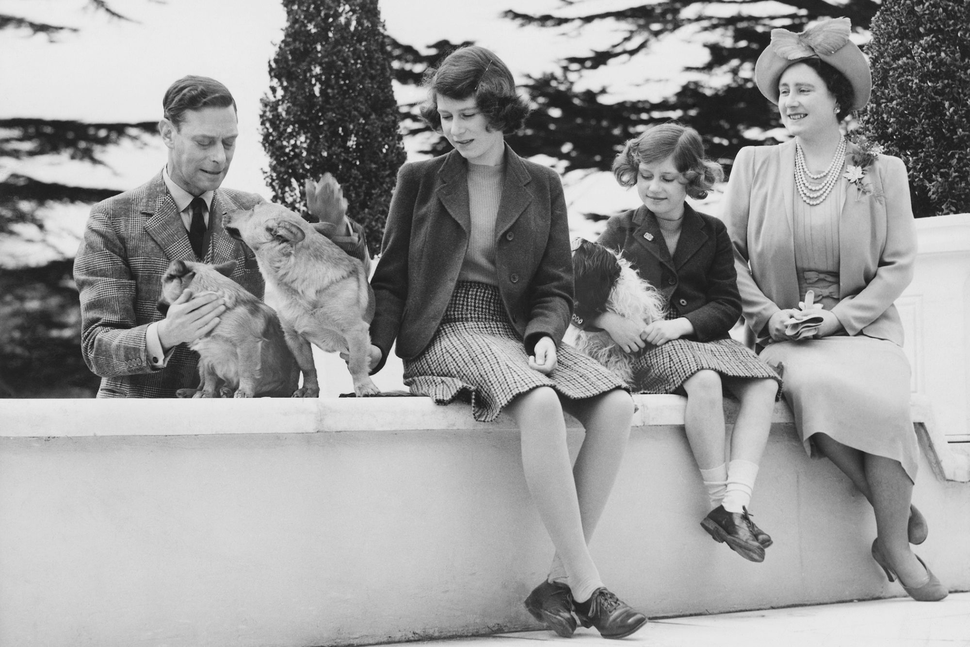 Teenaged Queen Elizabeth sits on ledge while petting dogs with family
