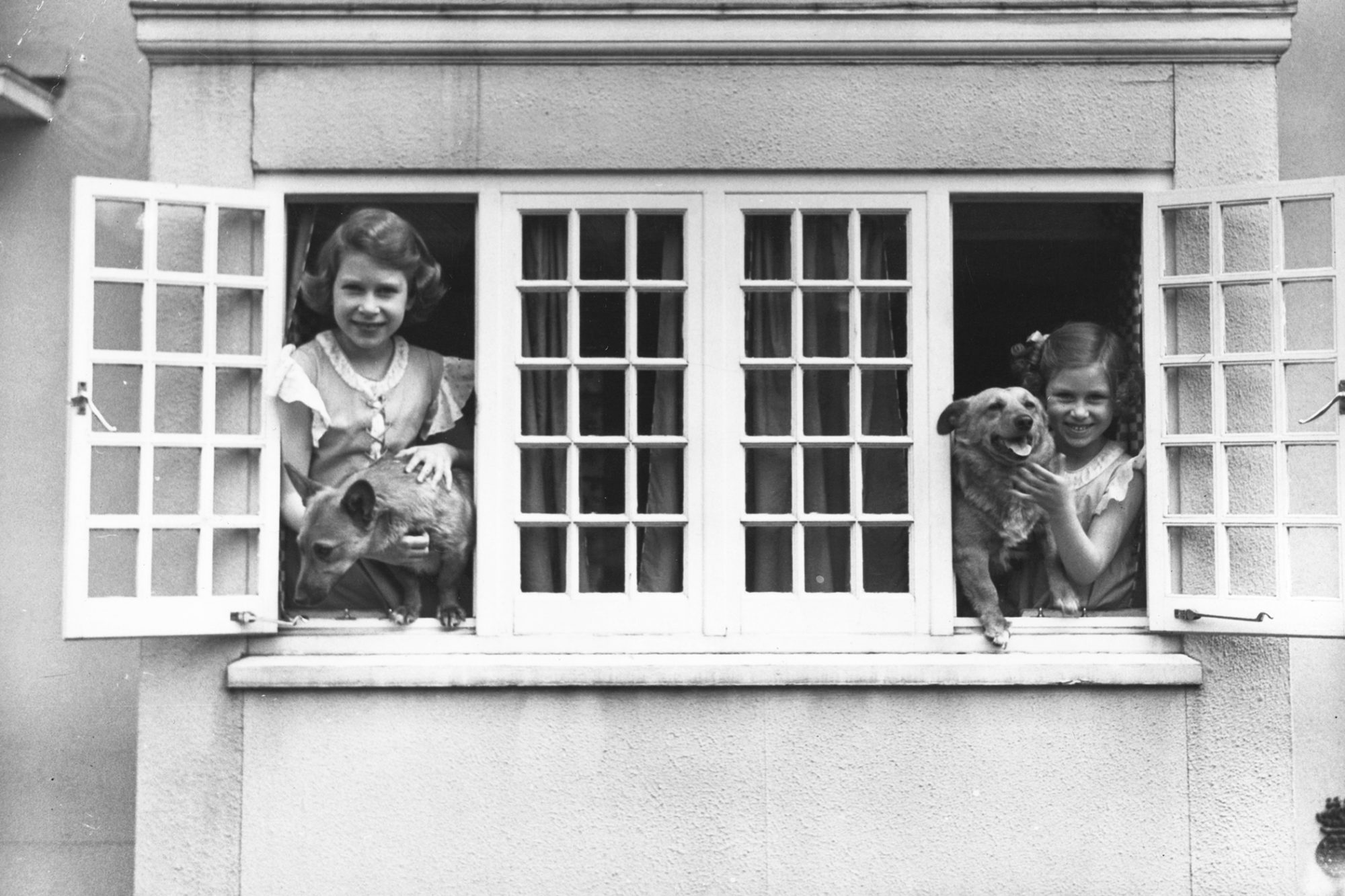 Black and white photo of Princess Elizabeth and other young girl holding dogs on windowsills