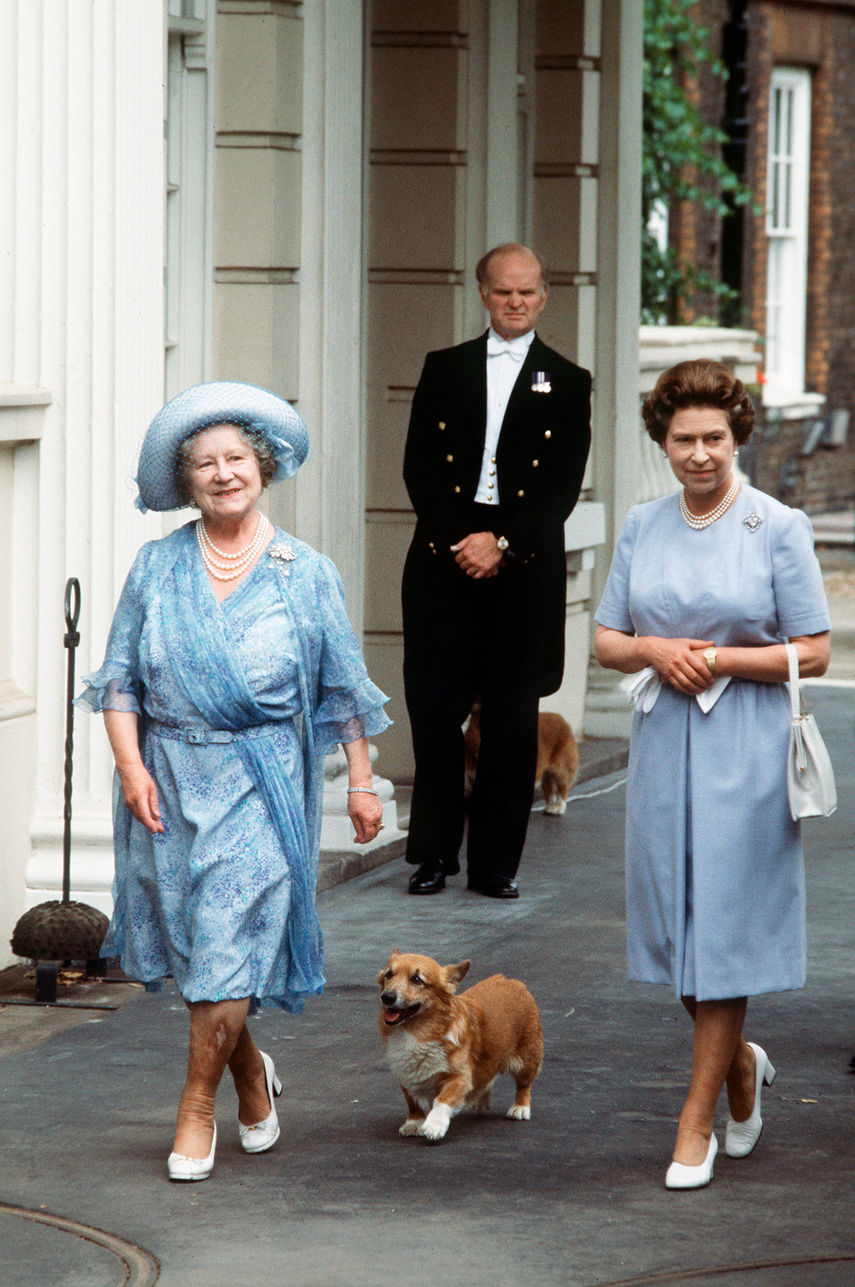 Queen Elizabeth and mother stroll down the street with an unleashed corgi