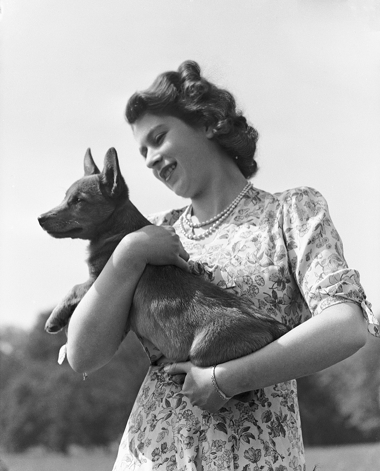 Black and white photo of teen princess elizabeth holding a corgi in arms