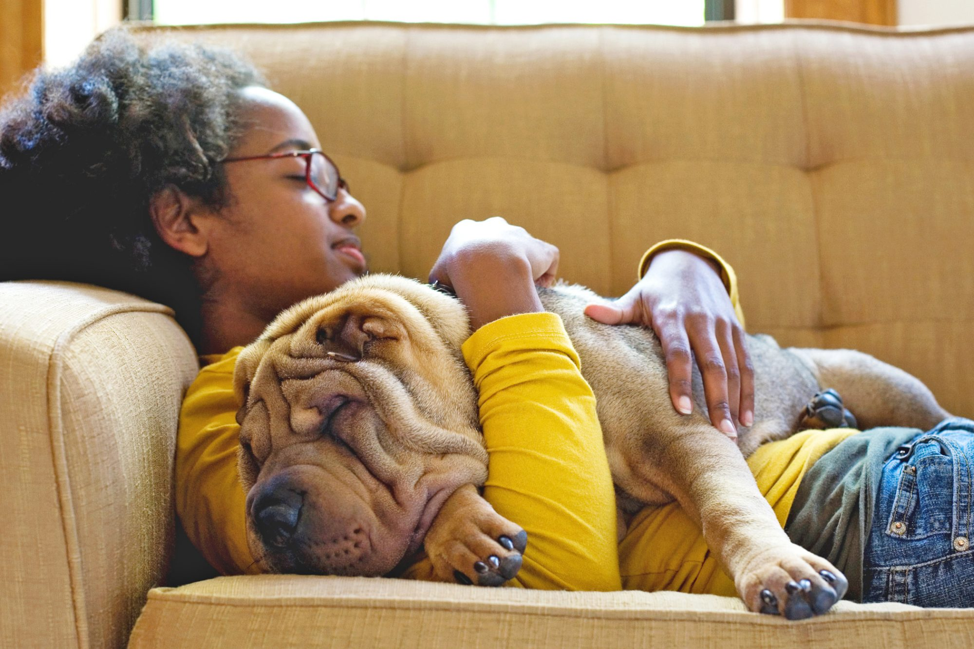 Young Black teen girl cuddles with tan shar-pei dog on tan couch