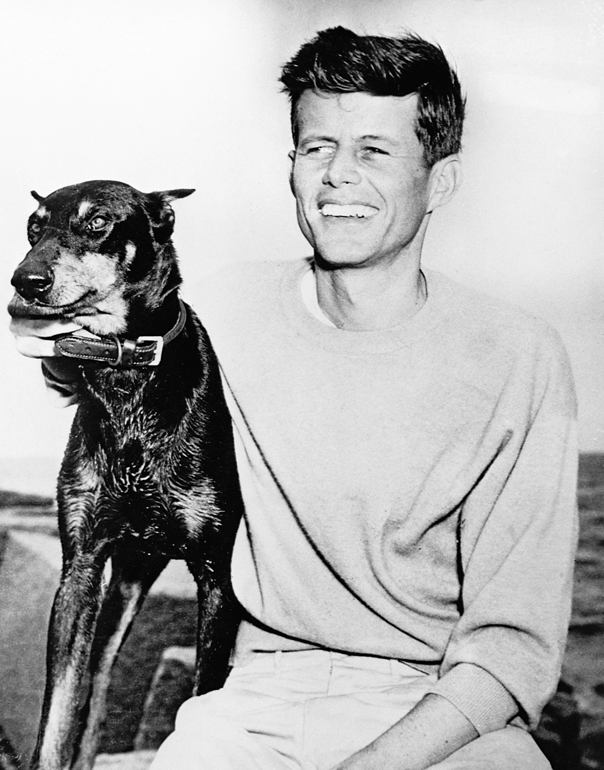 Black and white photo of John F. Kennedy embracing Doberman Pinscher dog while smiling