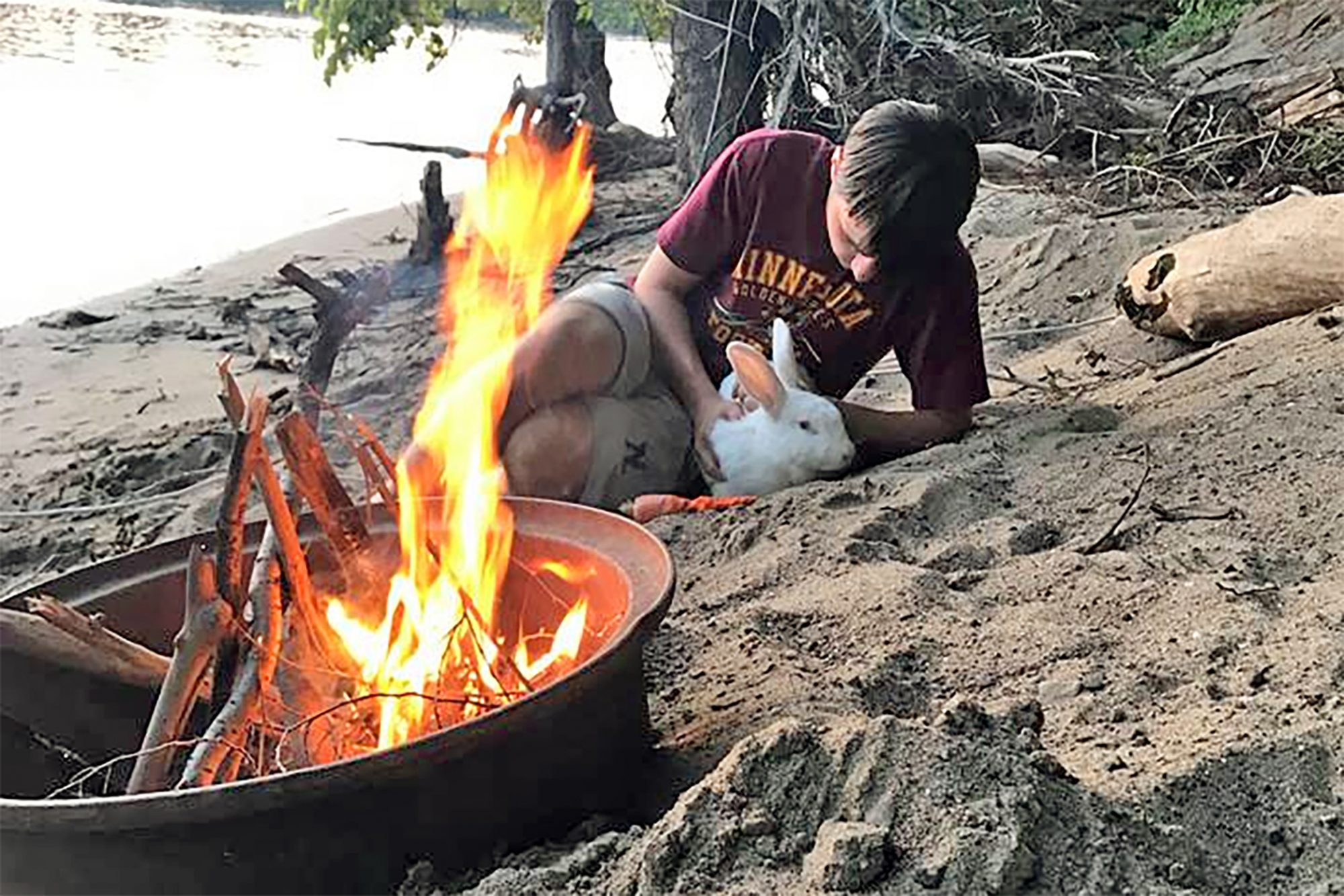 Caleb sitting on the beach with a white bunny in front of a fire