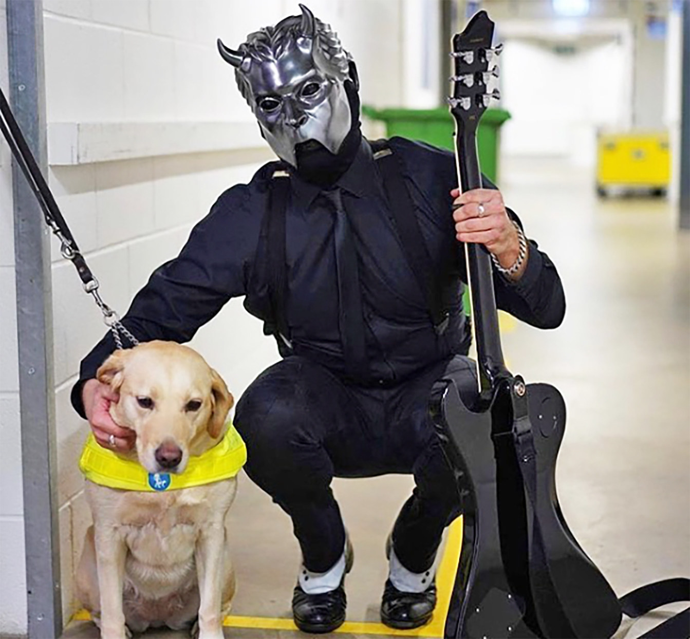 Yellow lab with yellow harness poses with a man in a heavy metal music costume
