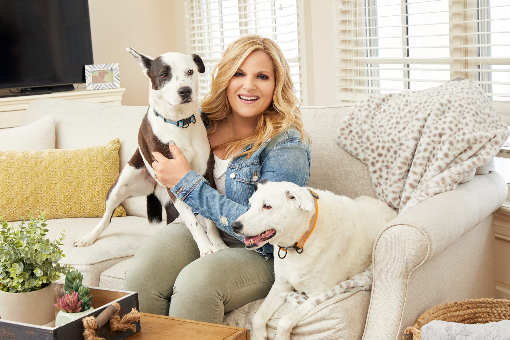 Influencer Trisha Yearwood poses with two adult dogs in living room