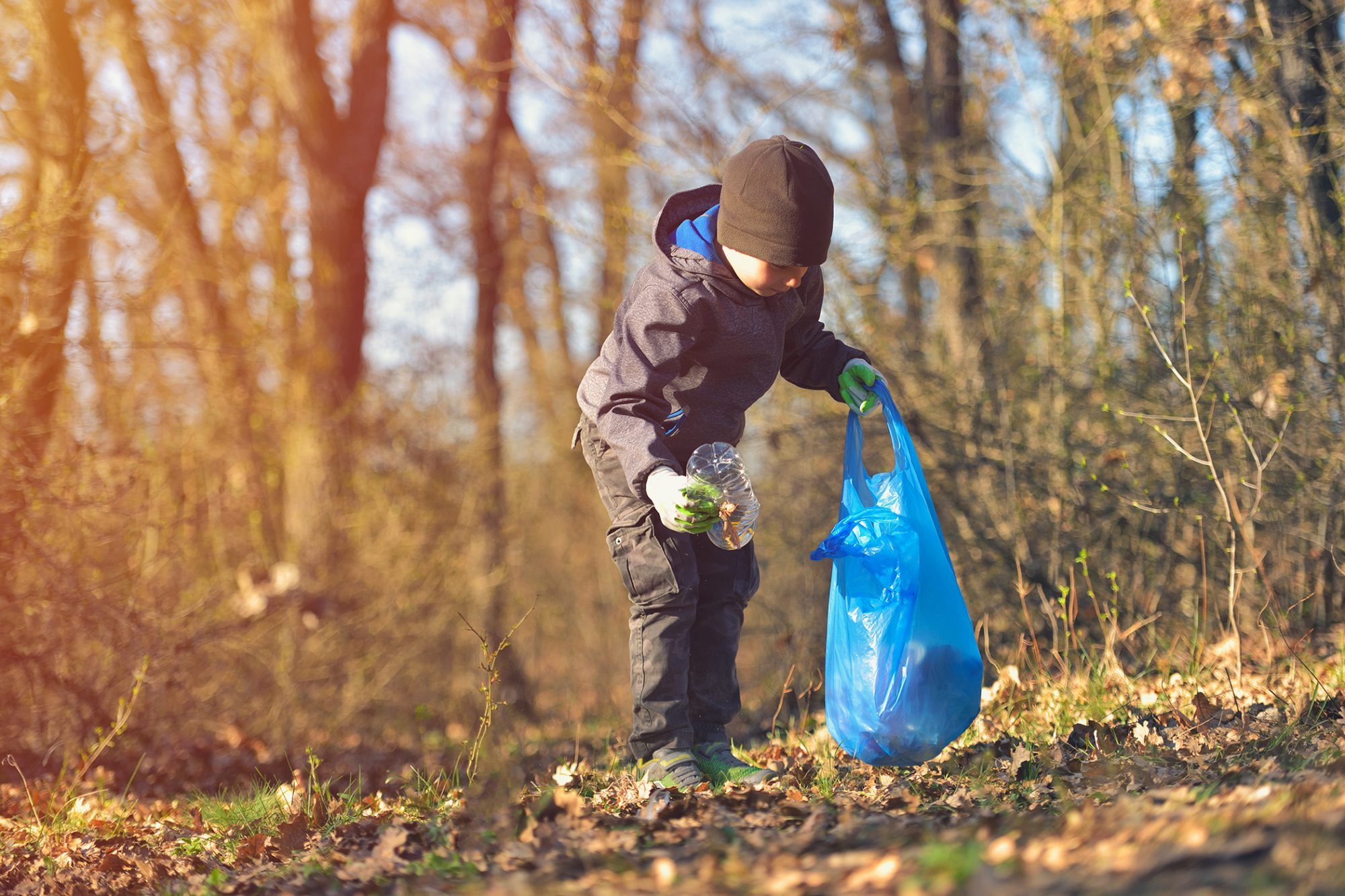Little boy picking up trash