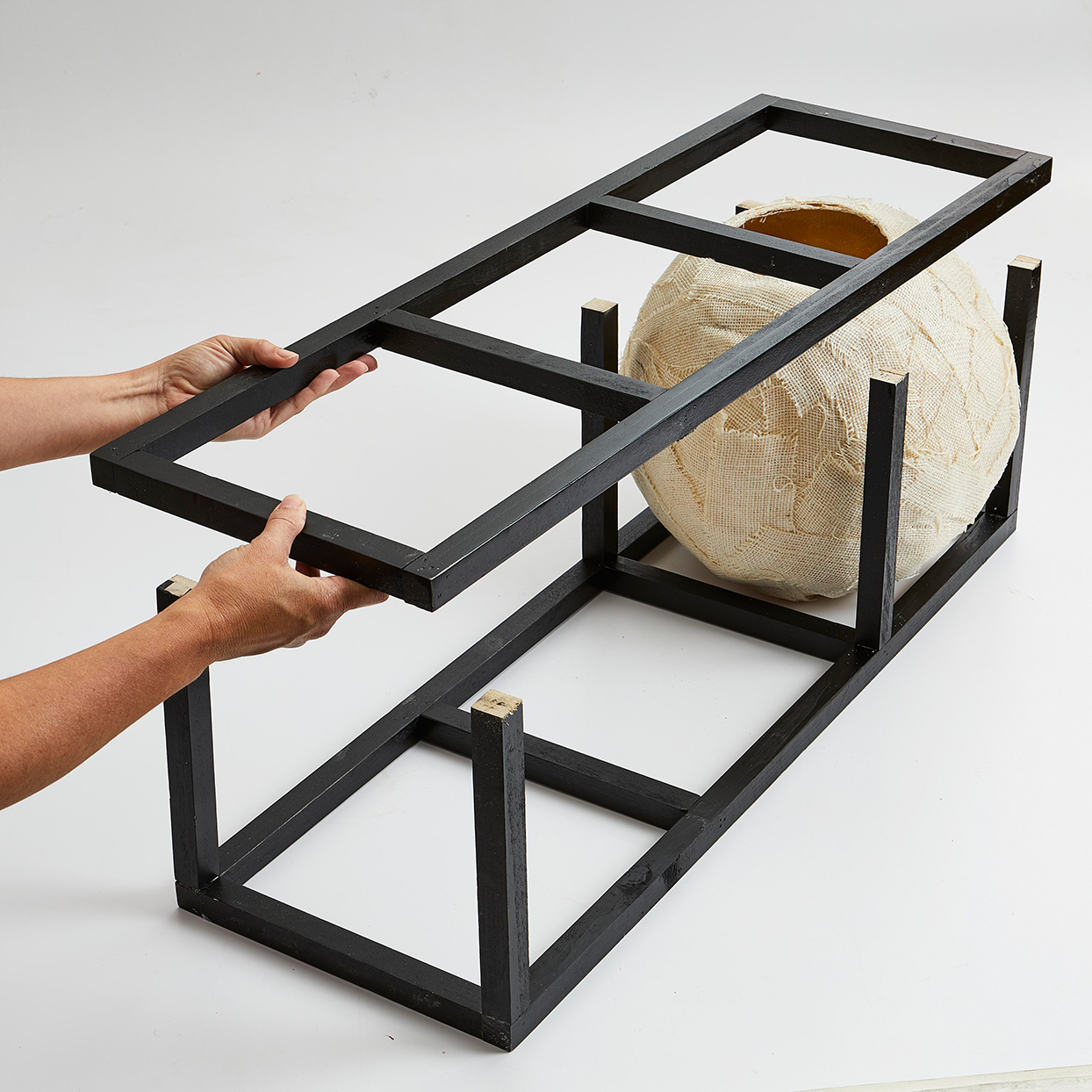 Adult hands put together cat tree with black frame and canvas bed