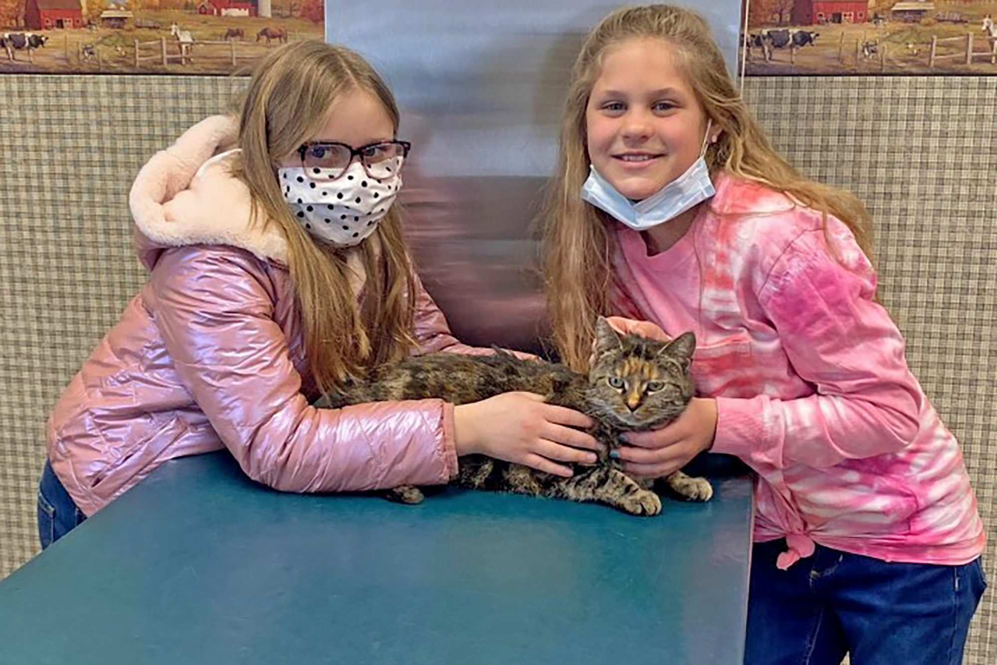 two girls holding cat