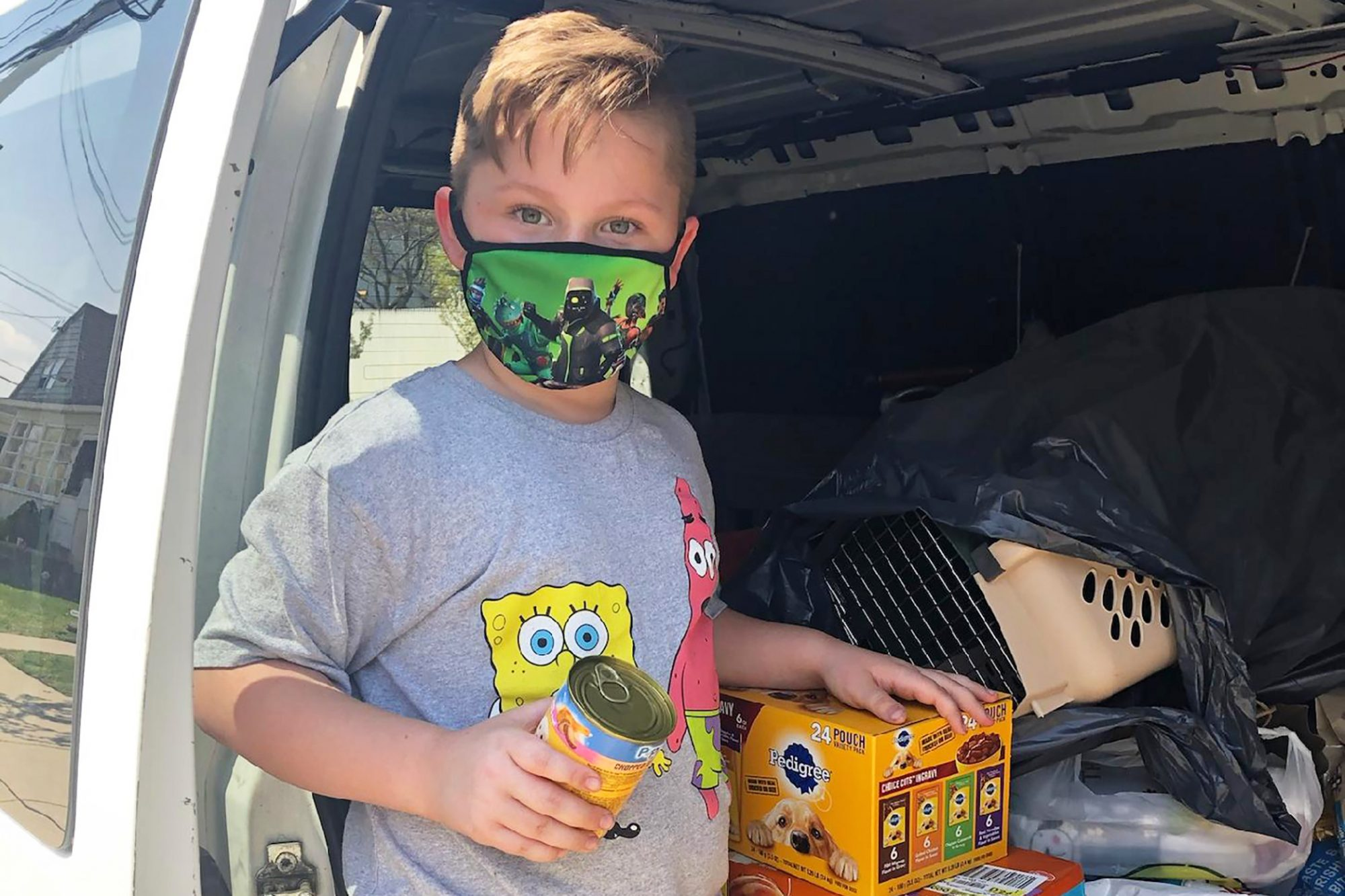 Conner in van with collection of pet food filled in the back