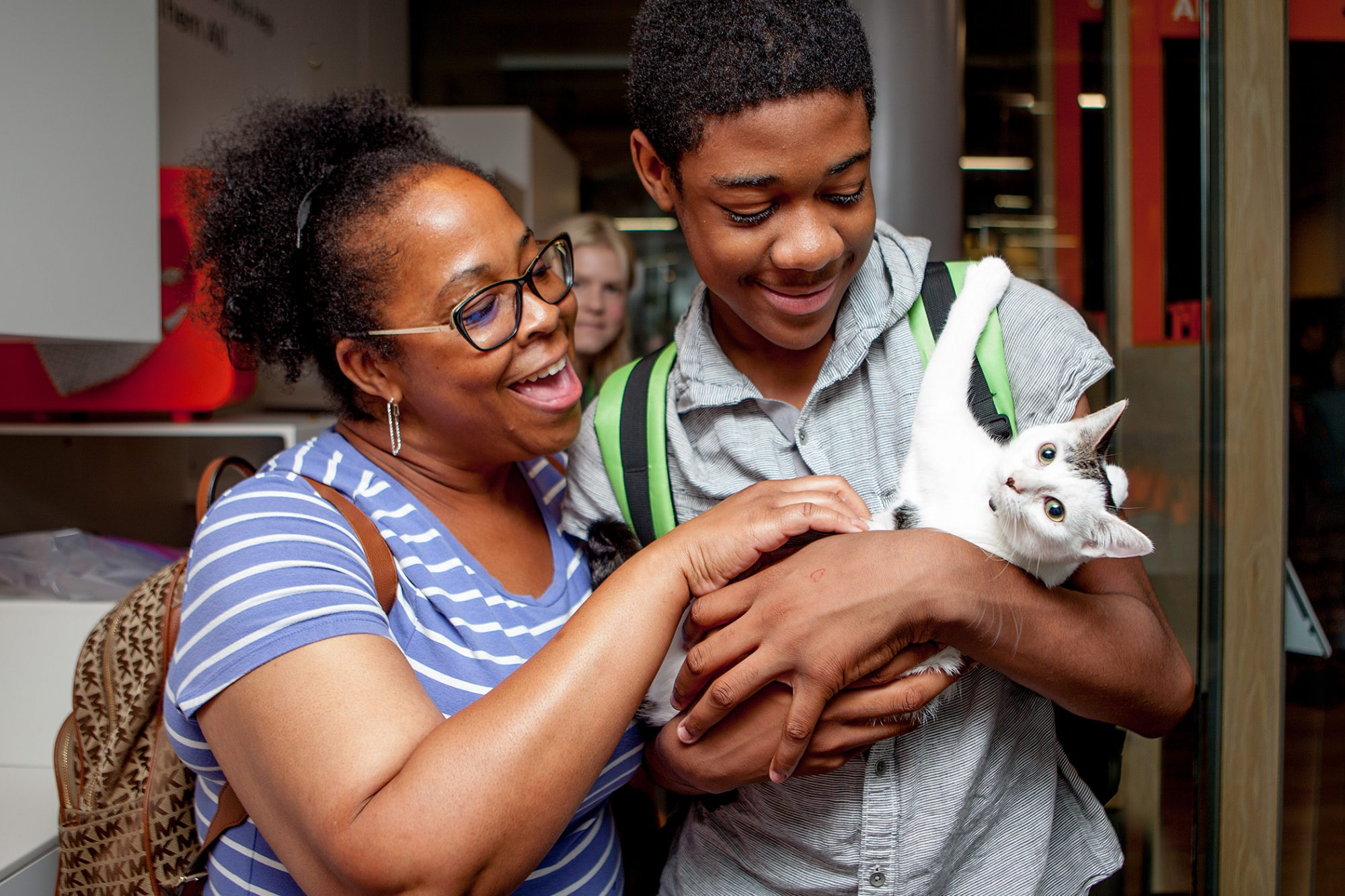 Woman and her son hold a white and grey kitten