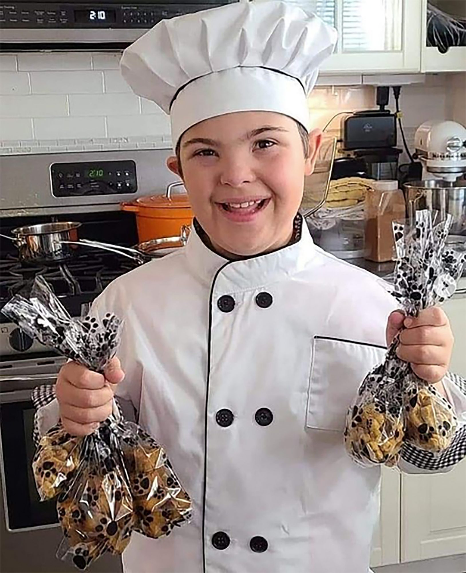 Connor wearing a chef's hat and holding bags of cookies