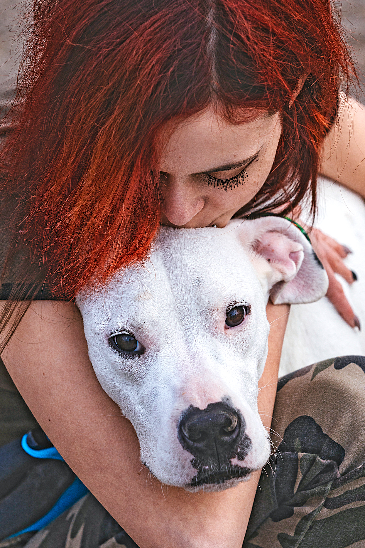 woman with dyed red hair hugging and kissing her dogo argentino on the head