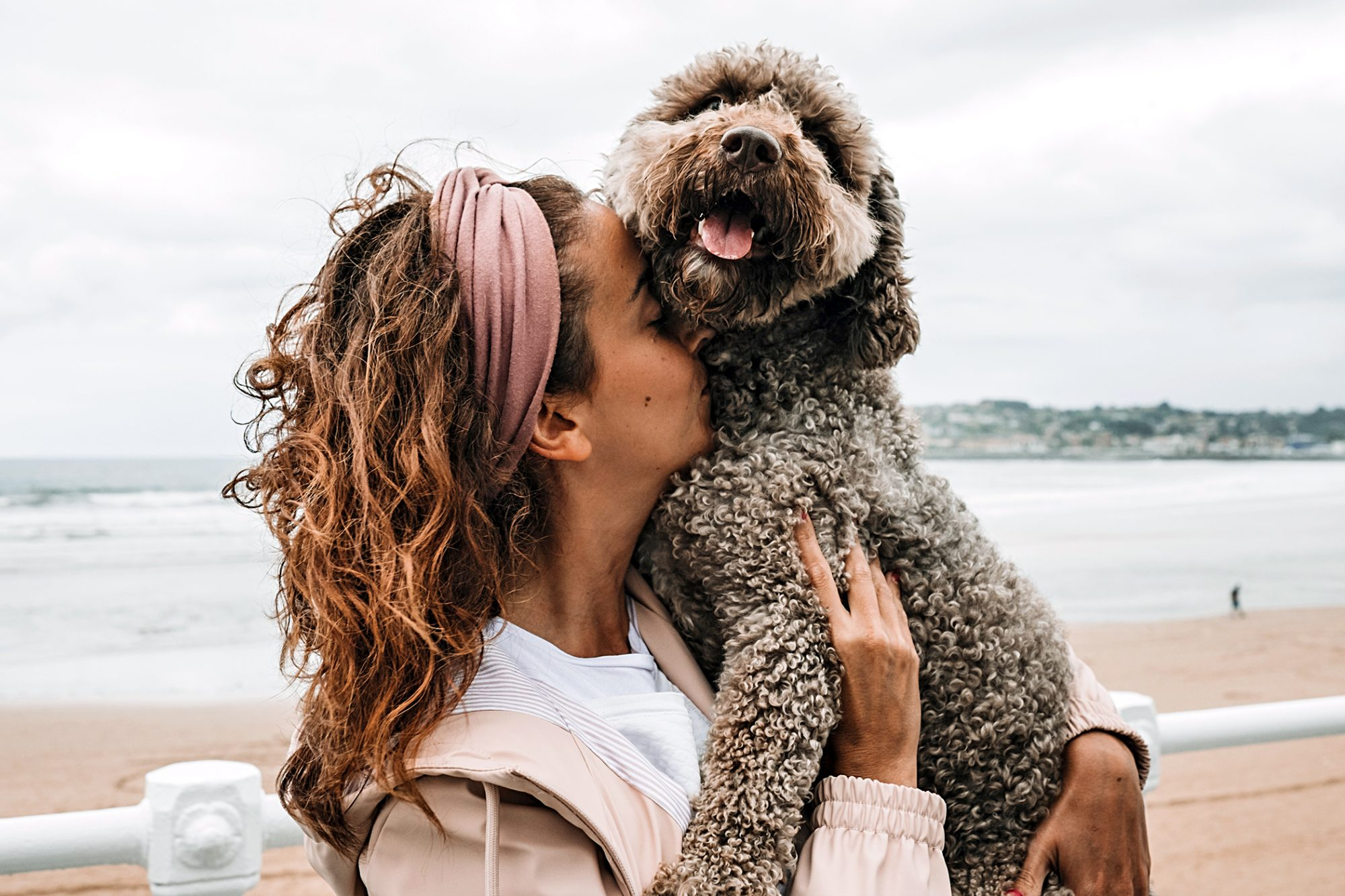 owner holding spanish water dog in her arms at the beach