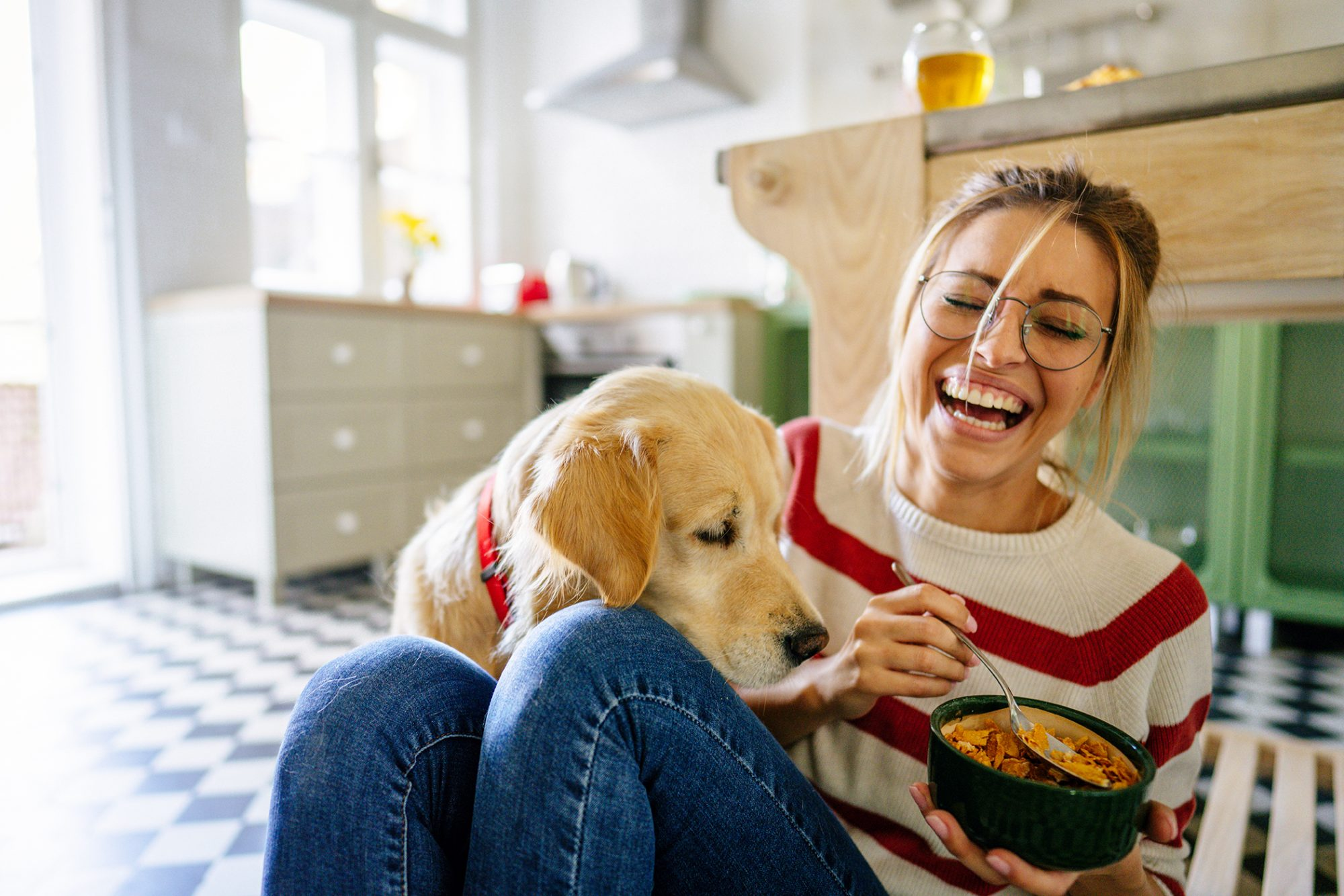woman sitting on kitchen floor laughing and eating food next to her dog