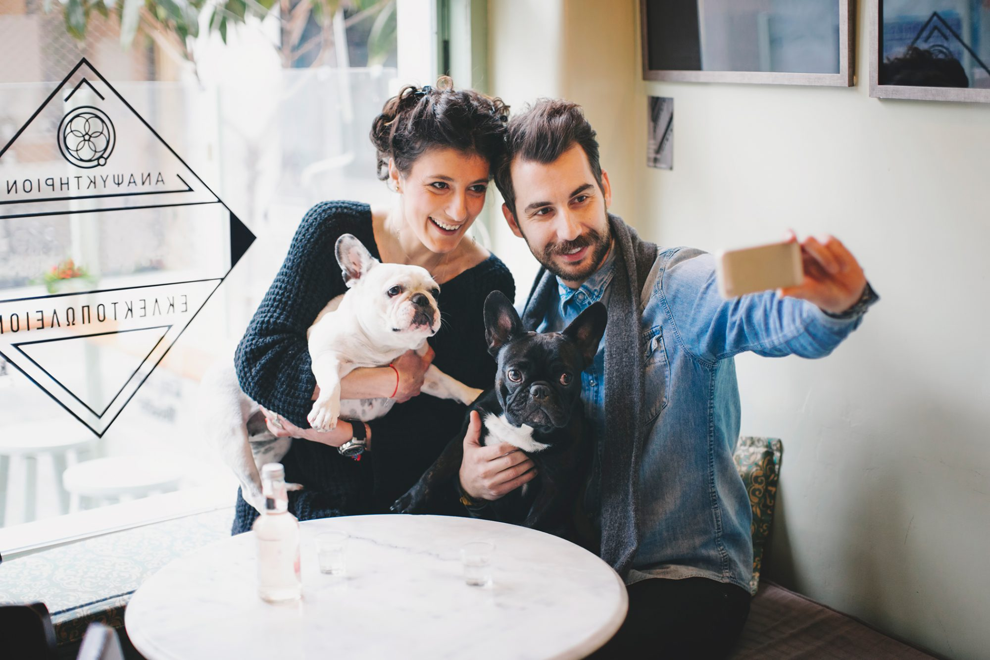 young greek couple taking selfie with their french bulldogs in a greek cafe