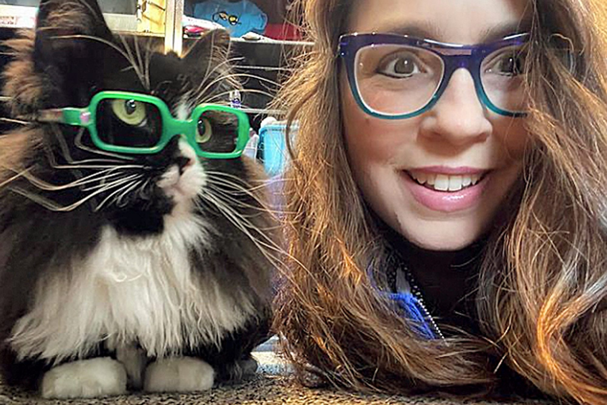 truffles the glasses cat wearing neon green glasses and his owner Danielle