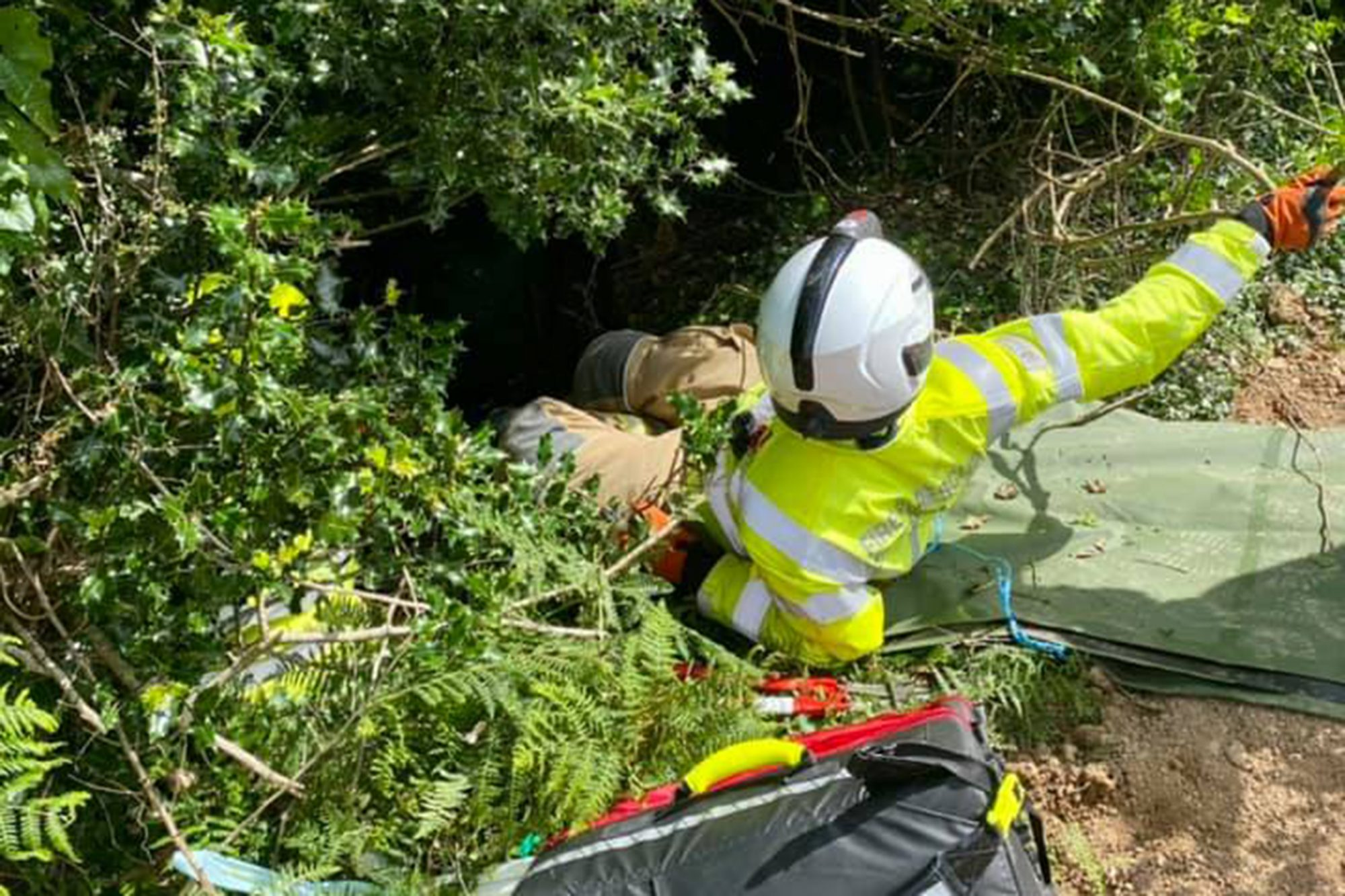 rescuer going down embankment where woman fell down