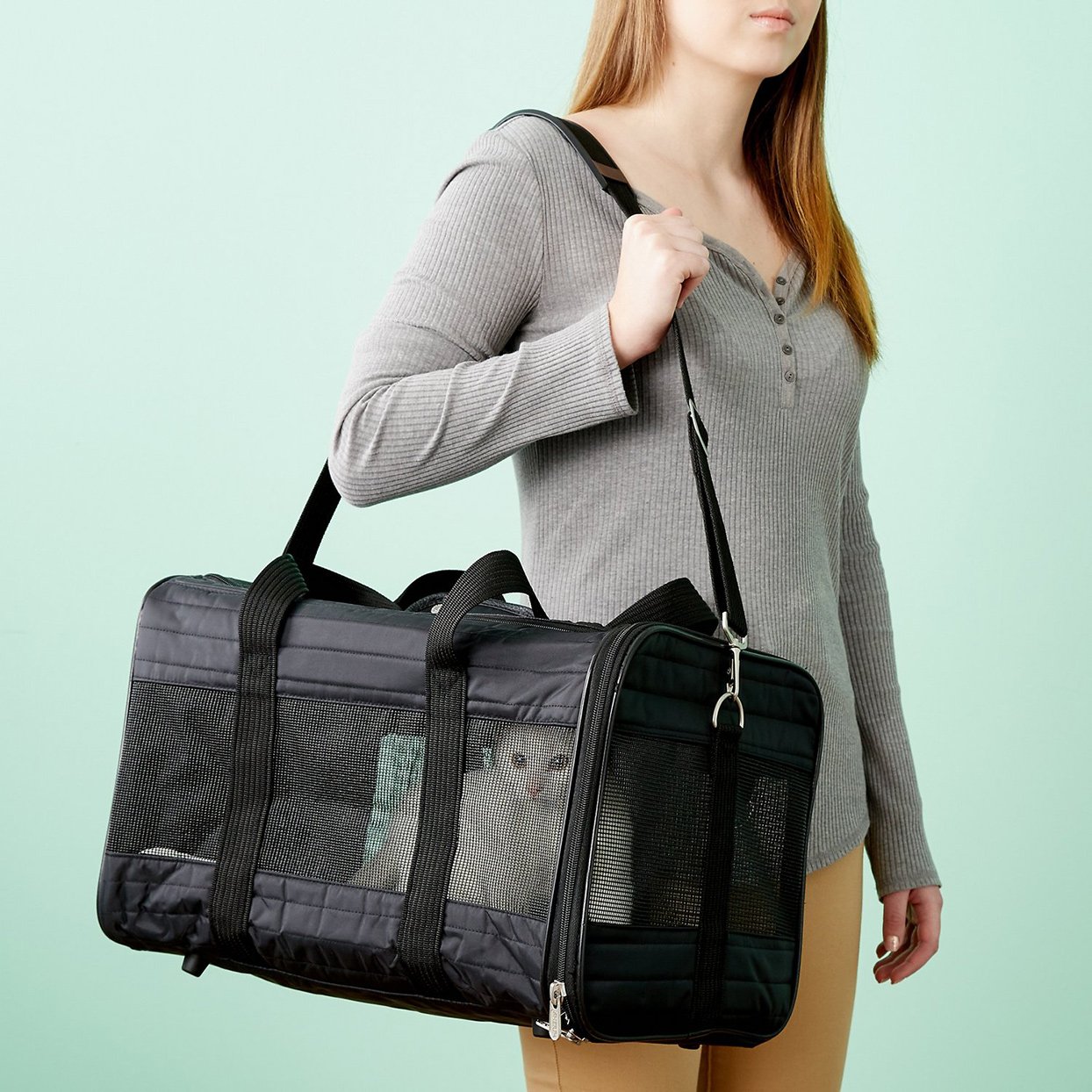Woman carrying a Sherpa Original Deluxe Airline-Approved Dog & Cat Carrier Bag on her shoulder