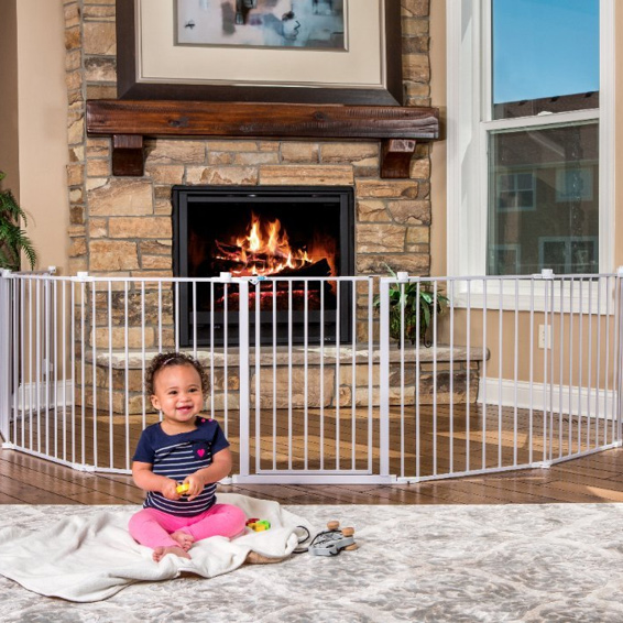 Baby sitting in from of a Regalo 192-Inch Super Wide Adjustable Baby Gate and Play Yard blocking a fireplace