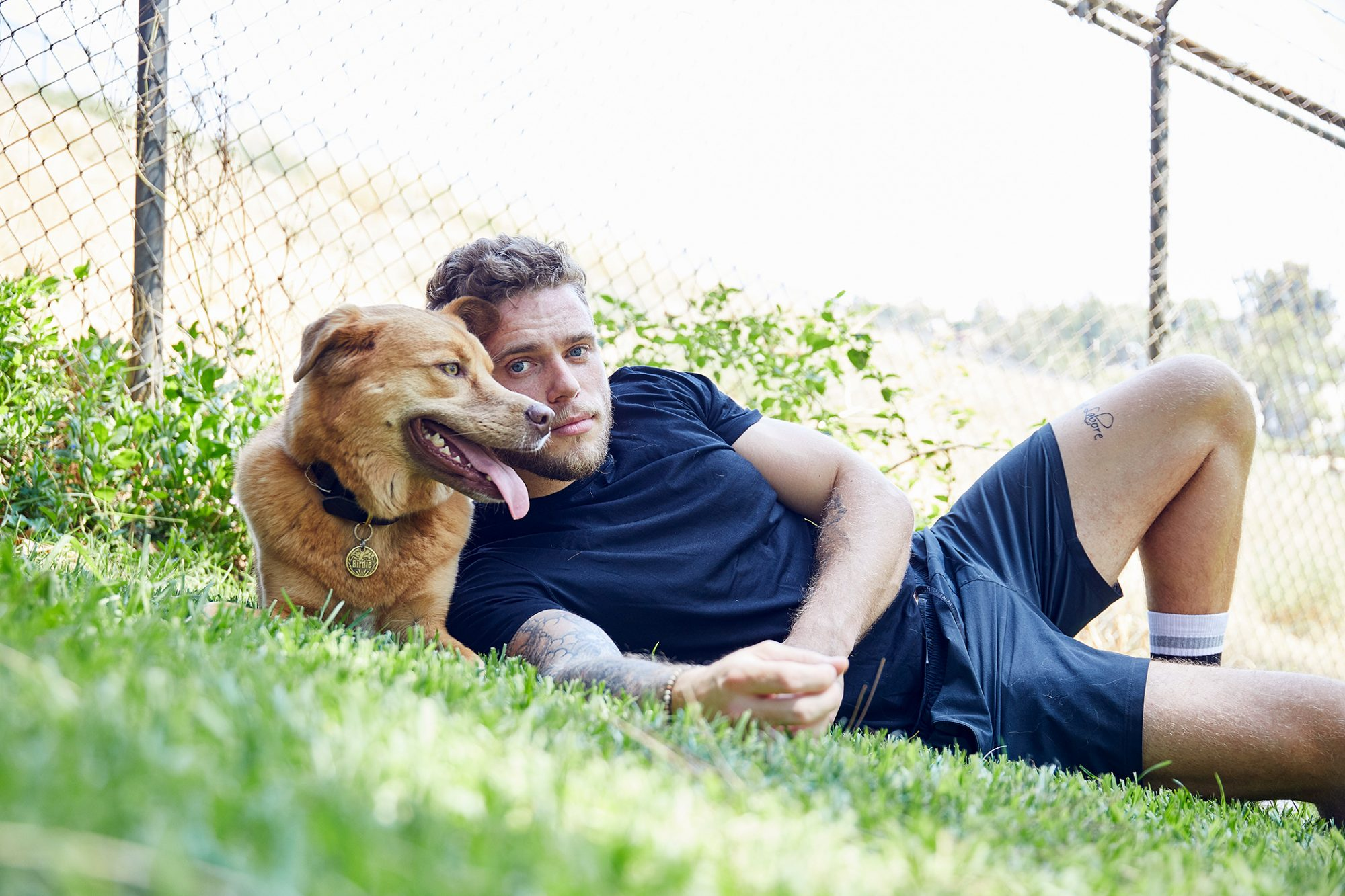 Gus Kenworthy laying in grass with Birdie