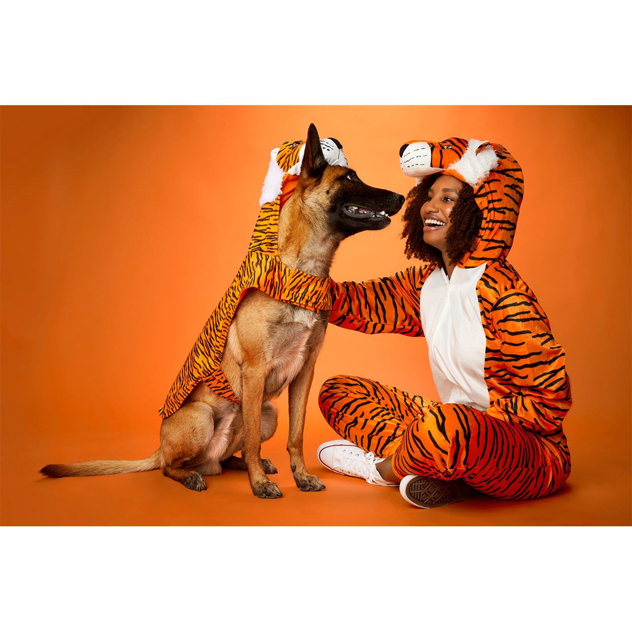 person and dog in tiger costumes