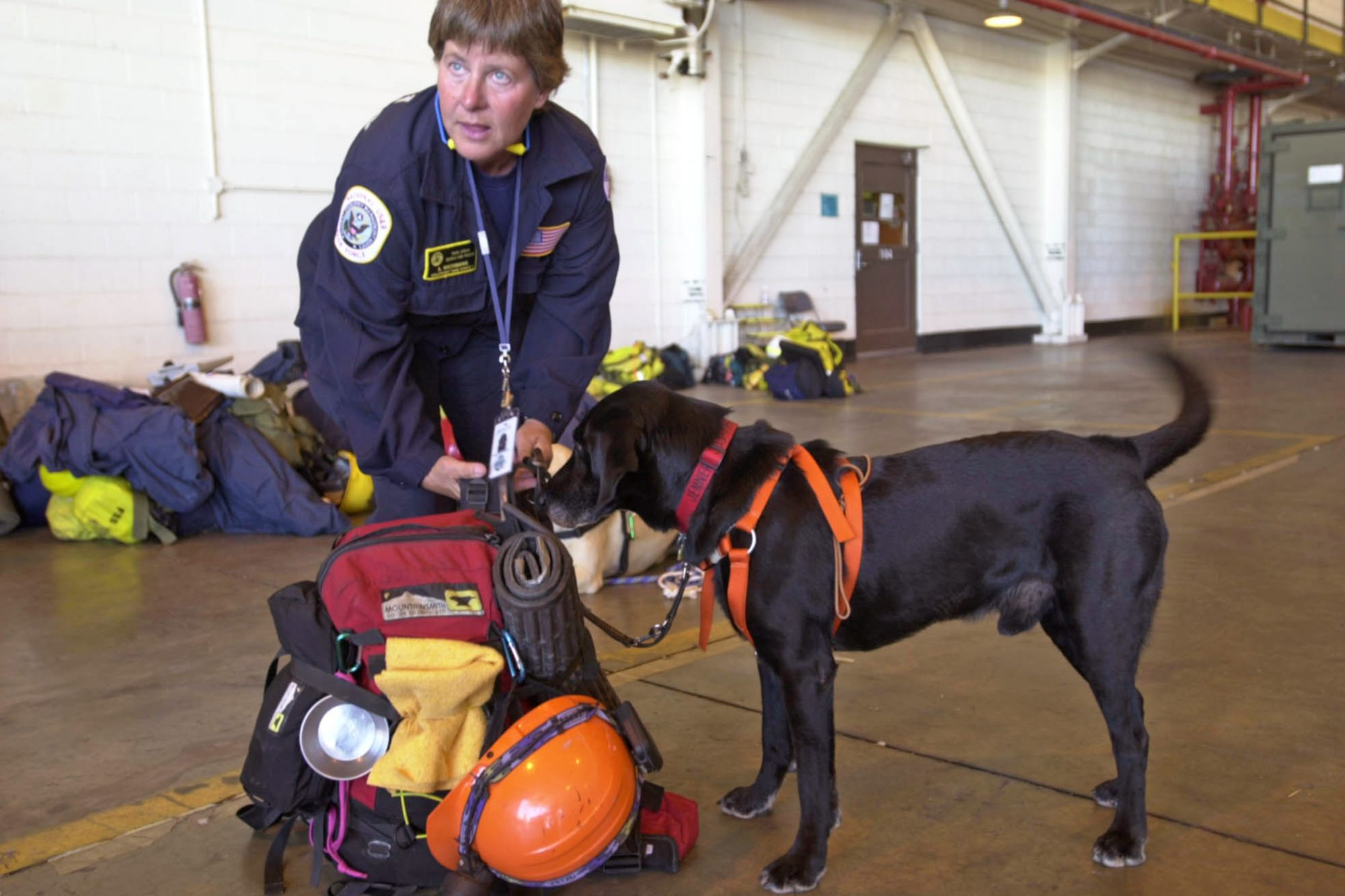 9/11 service dog Jenner standing with Ann Wichmann indoors