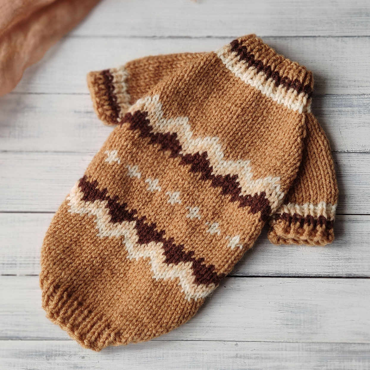 Brown patterned knit dog sweater that looks like Bernie Sanders' mittens from the 2021 presidential inauguration