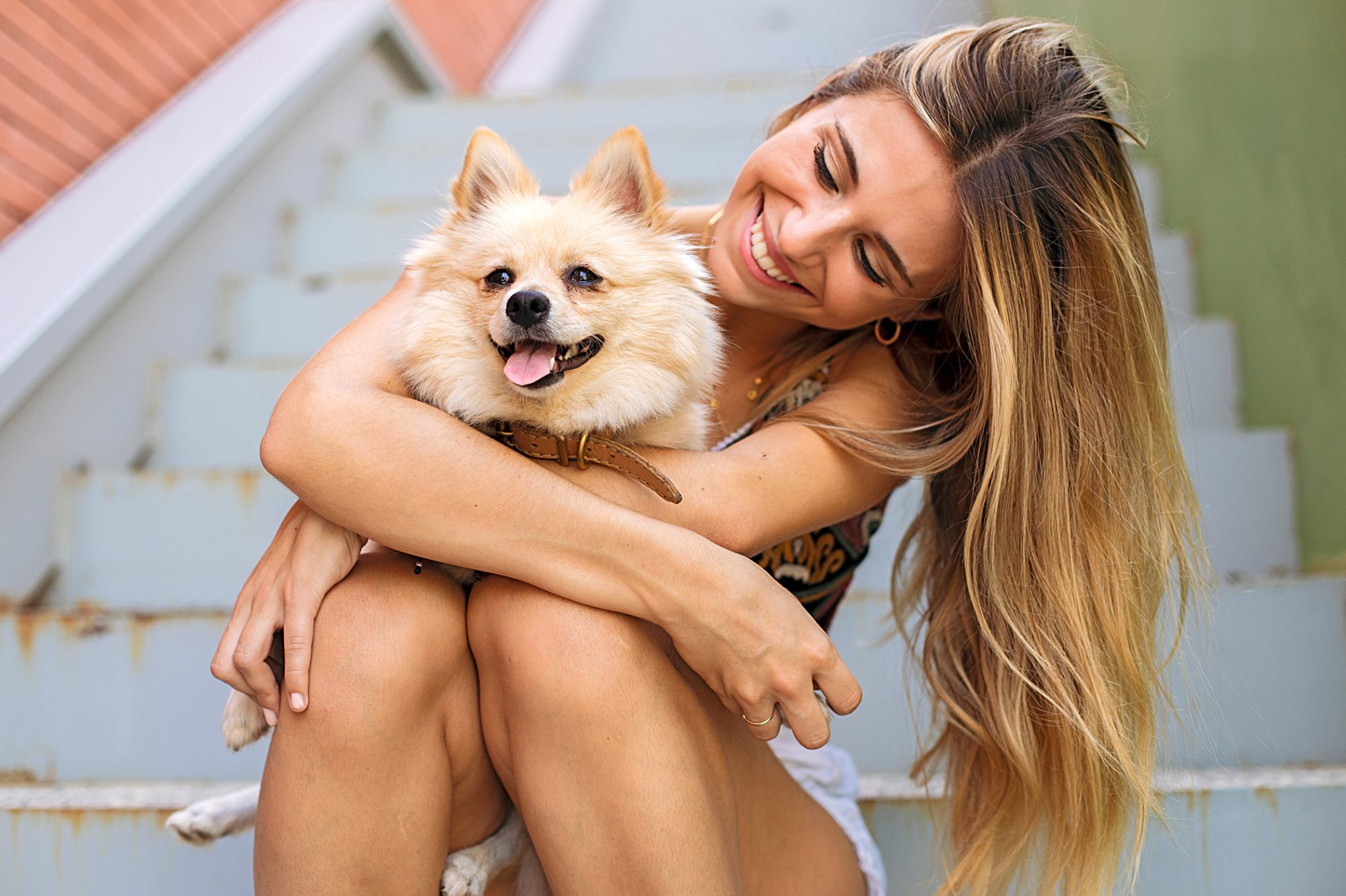blonde woman holding her german spitz while sitting on a staircase