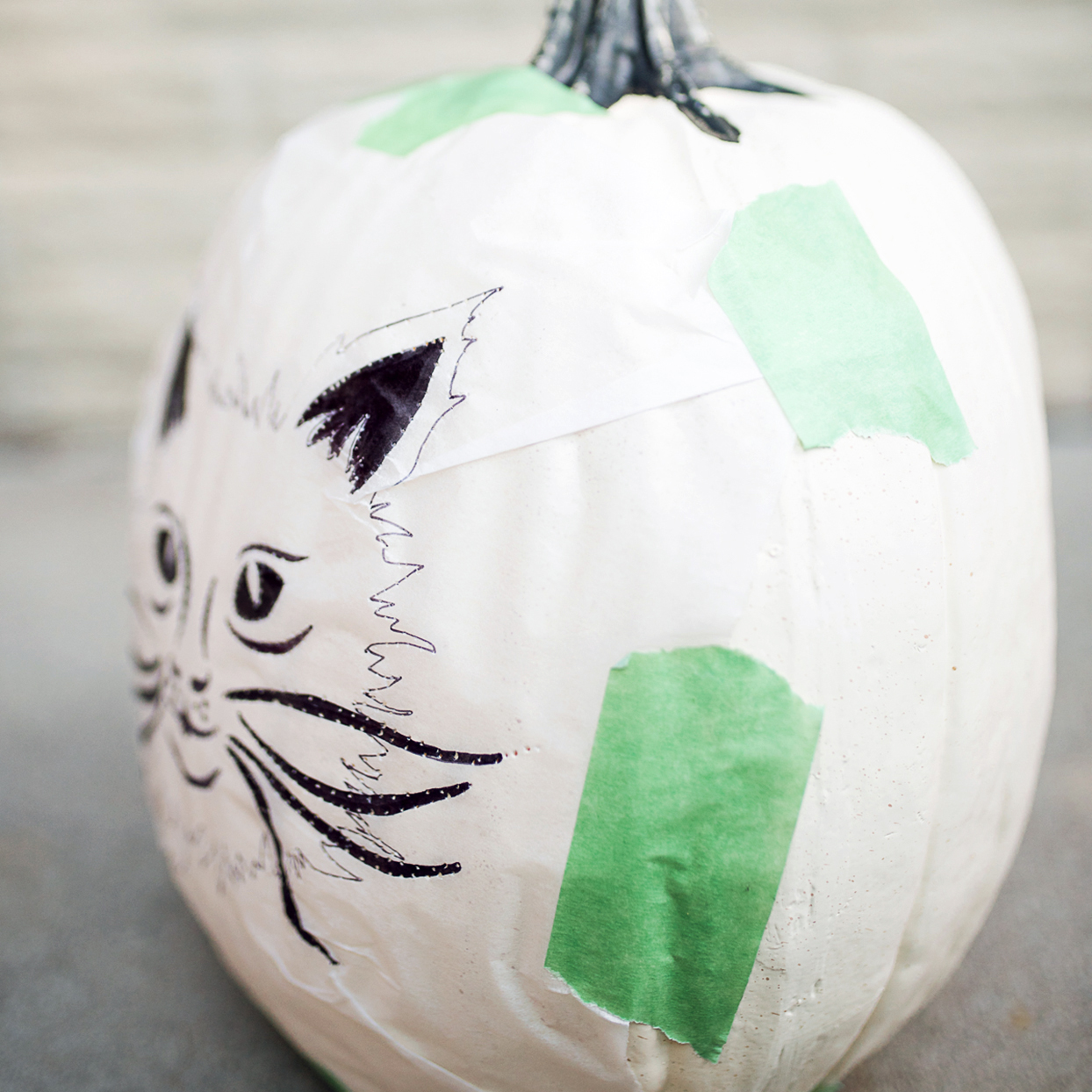 cat drawing stencil taped onto a white pumpkin with green painters tape