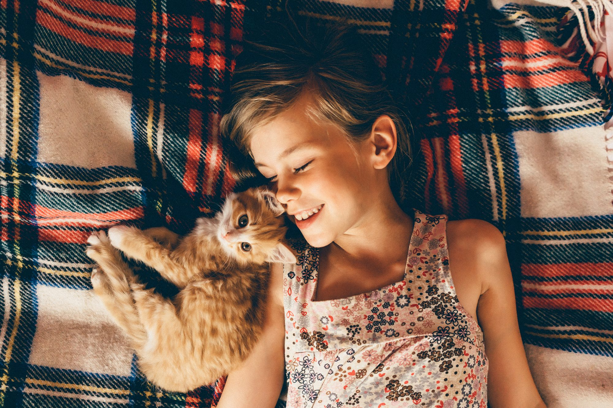 child lying with their orange striped kitten on a plaid bed spread