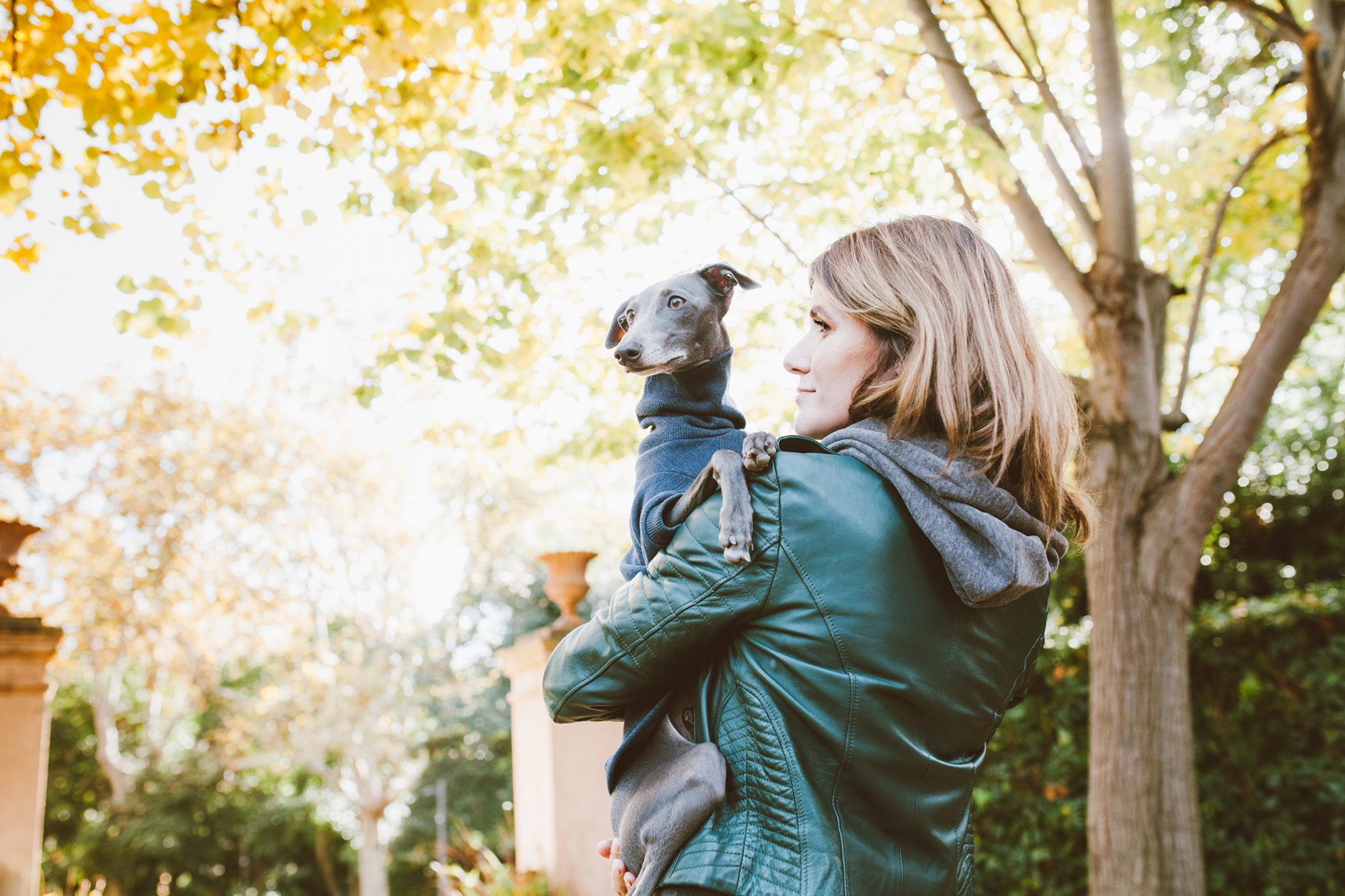woman wearing a leather jacket holding an italian greyhound wearing a turtleneck sweater outdoors