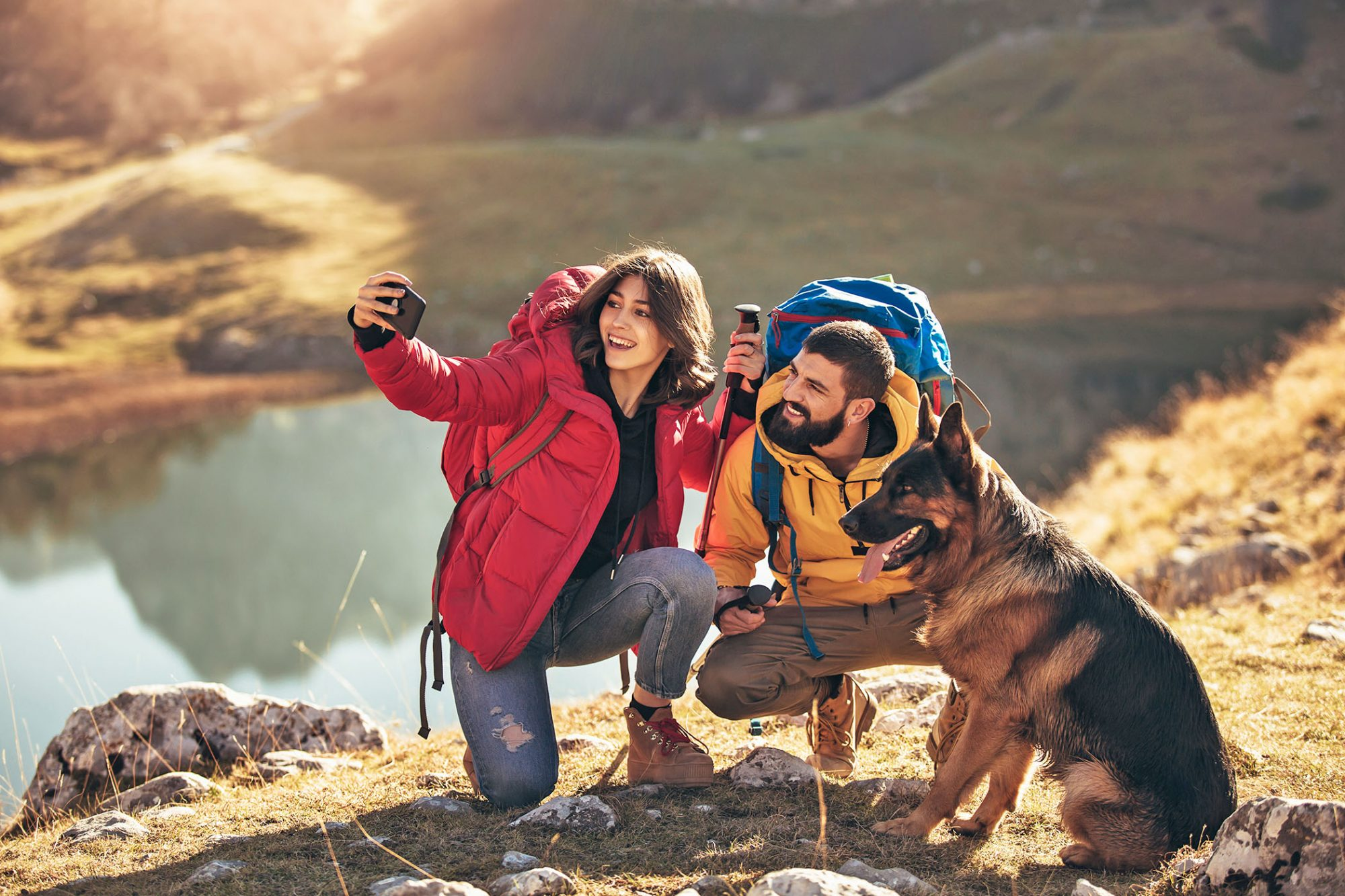 couple posing for a photo with their dog on a hike at a dog-friendly hiking spot