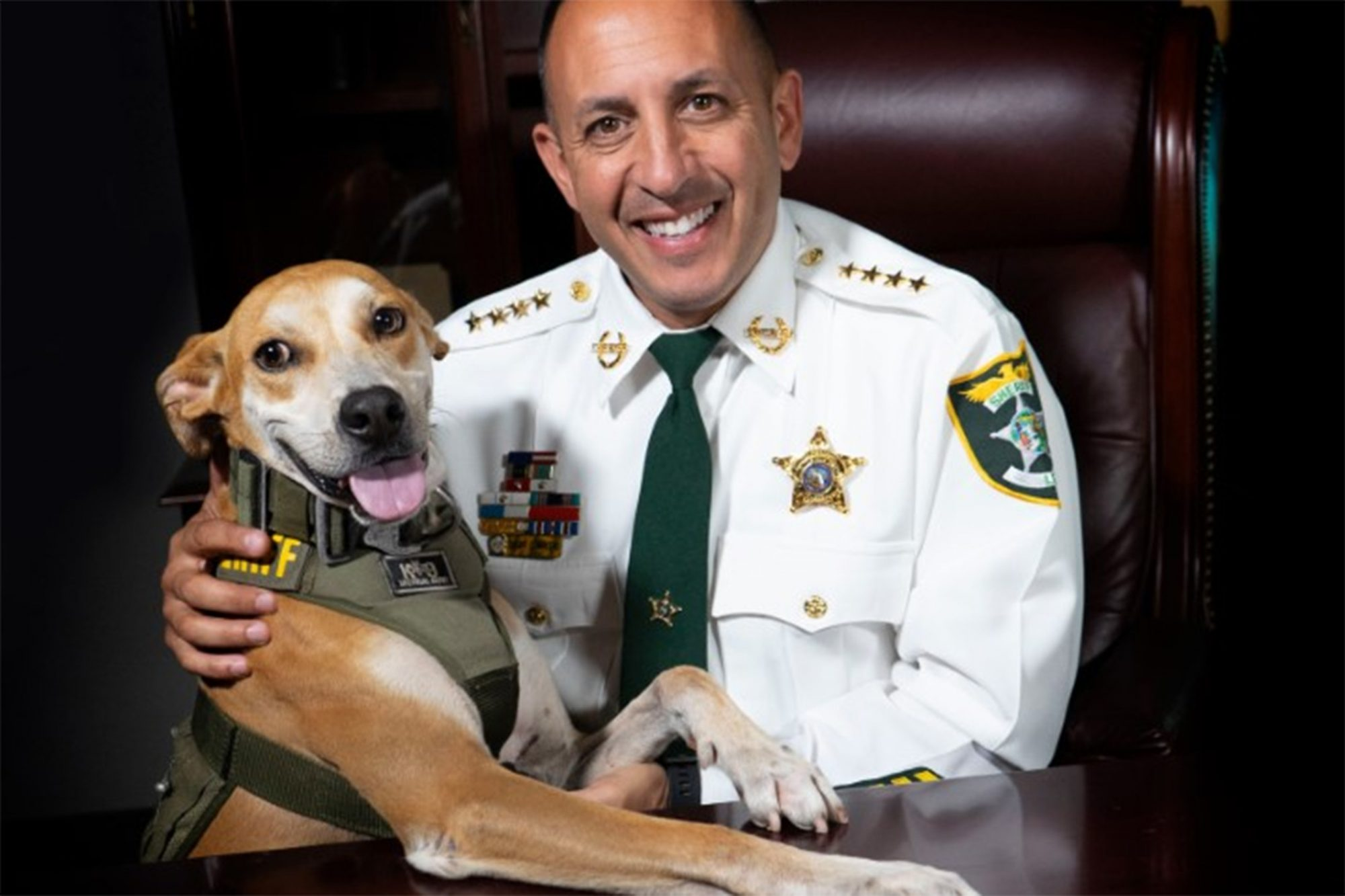 Deputy Chance, shelter dog of the year posing with Sheriff