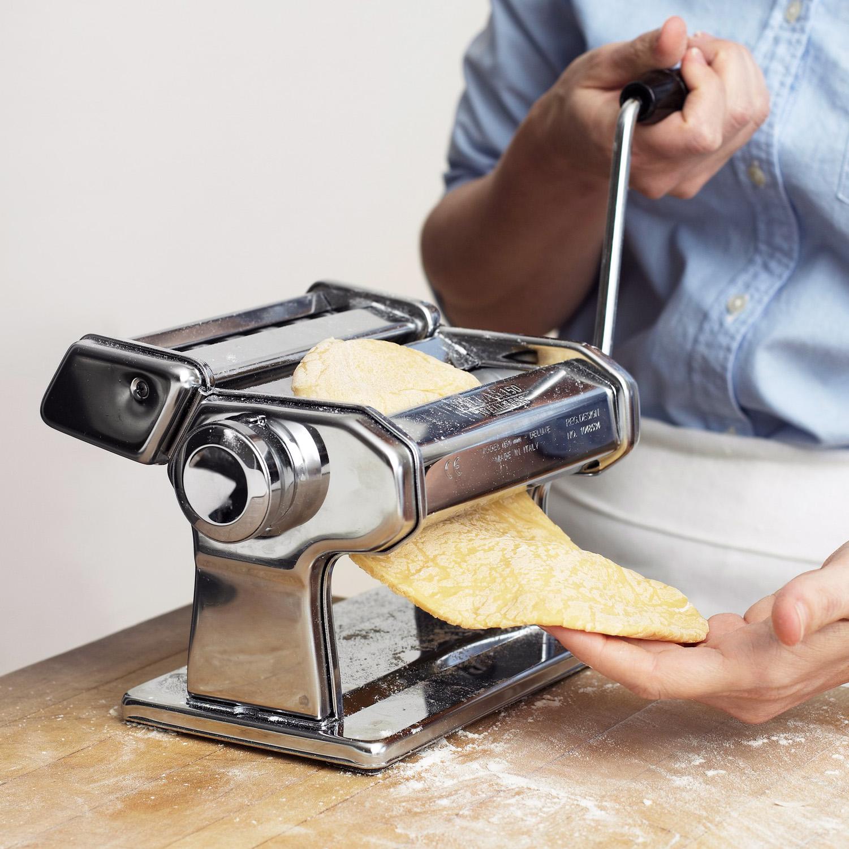 running pasta dough through pasta machine
