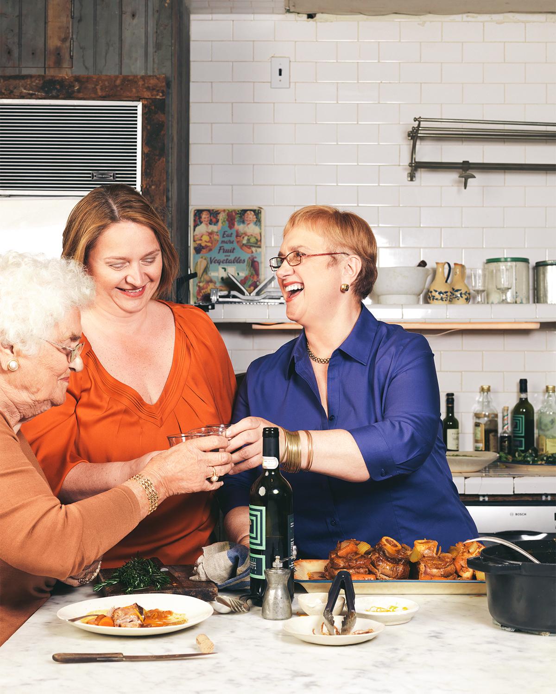 women toasting wine in kitchen