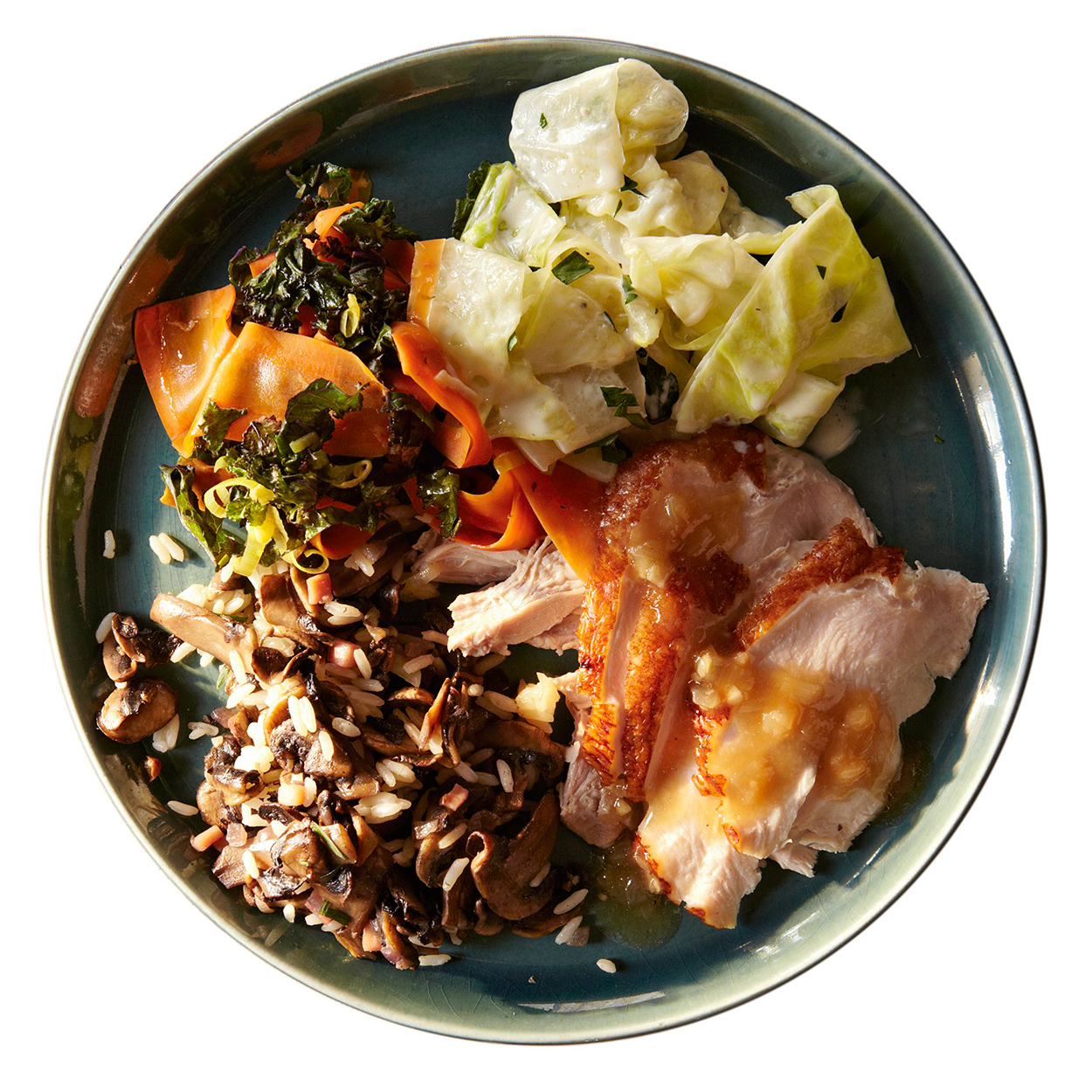 creamed cabbage, carrots and kale, wild rice stuffing and turkey on plate