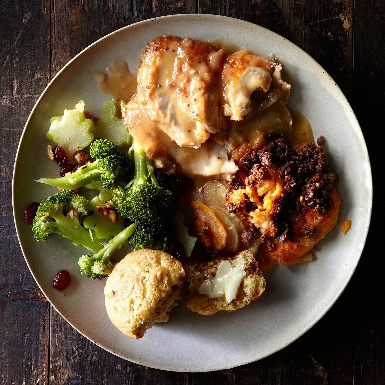 turkey, broccoli salad, sweet potatoes and muffin on plate
