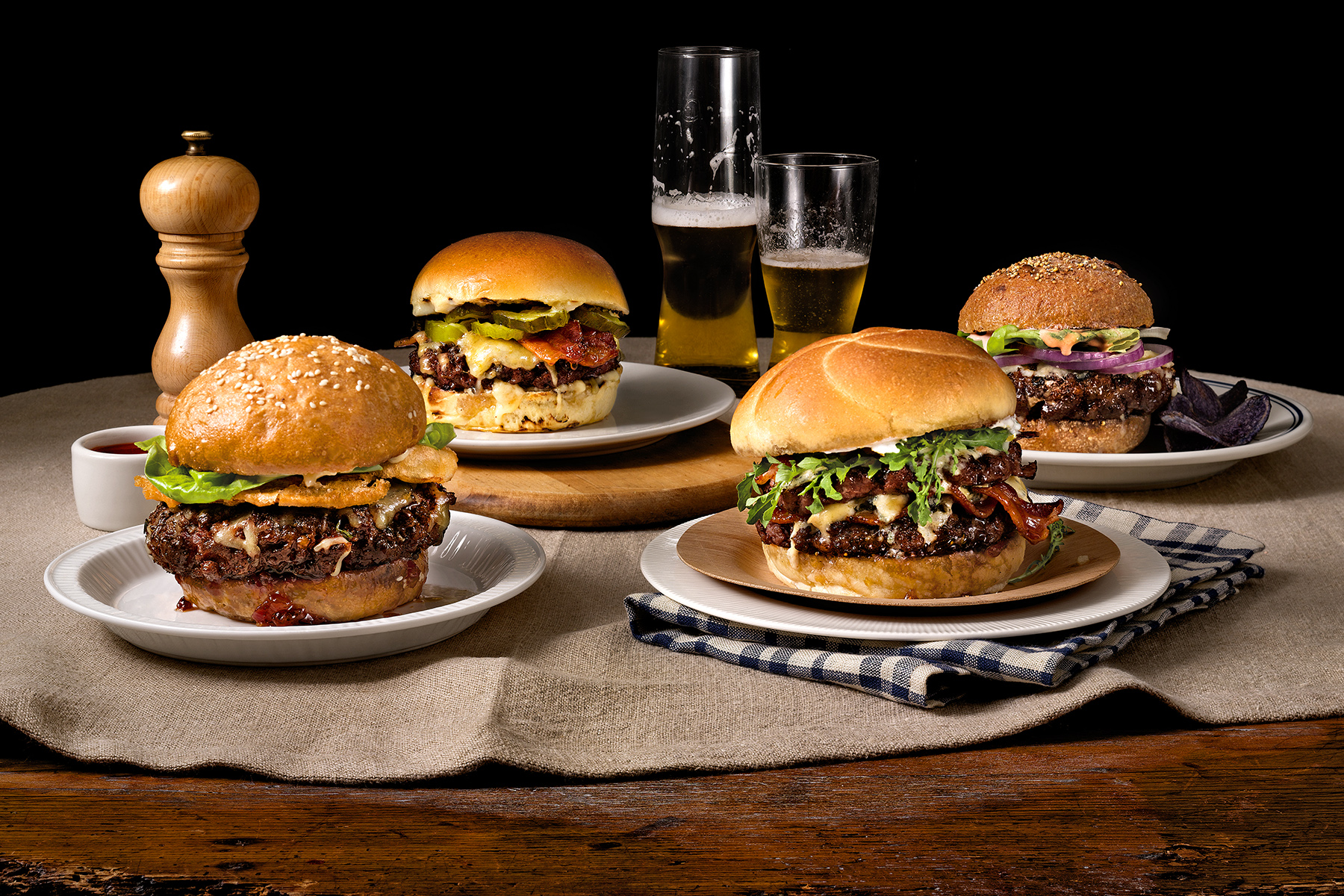 four artisan burgers on plate with beer