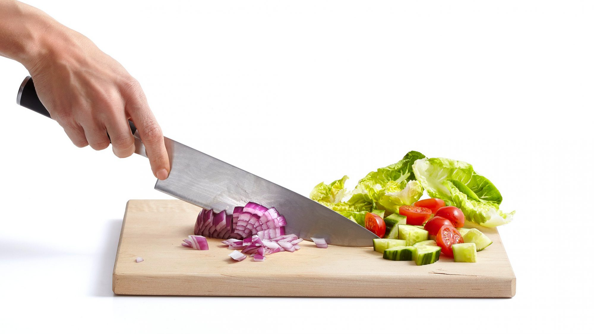 chopping onion lettuce cucumbers and cherry tomatoes on cutting board