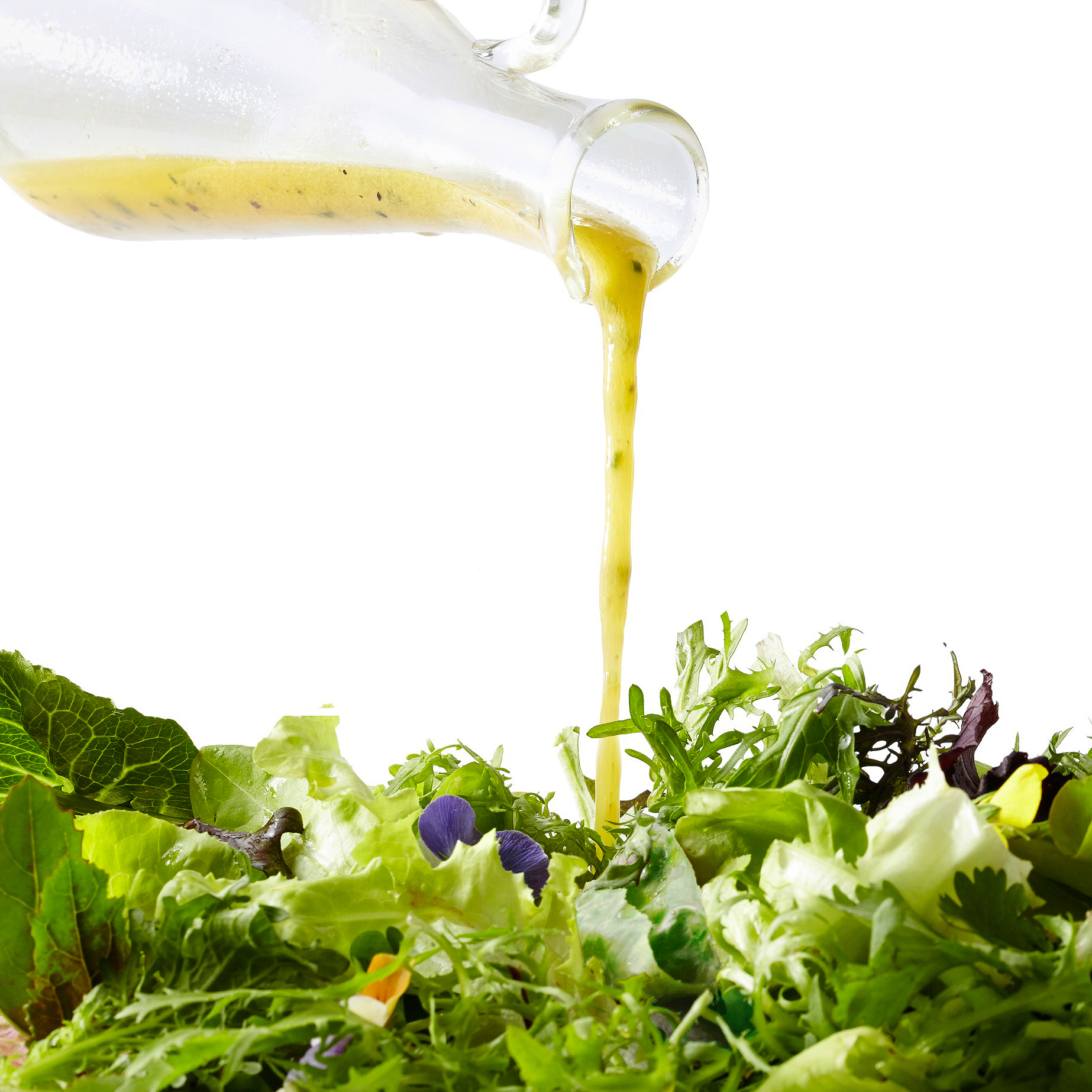 pouring salad dressing on a salad