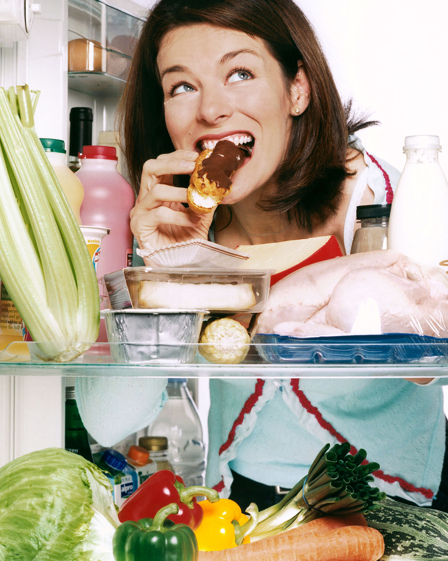 woman eating food from fridge