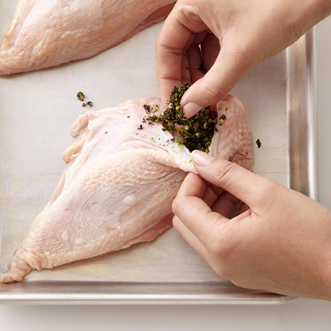stuffing chicken adding herbs