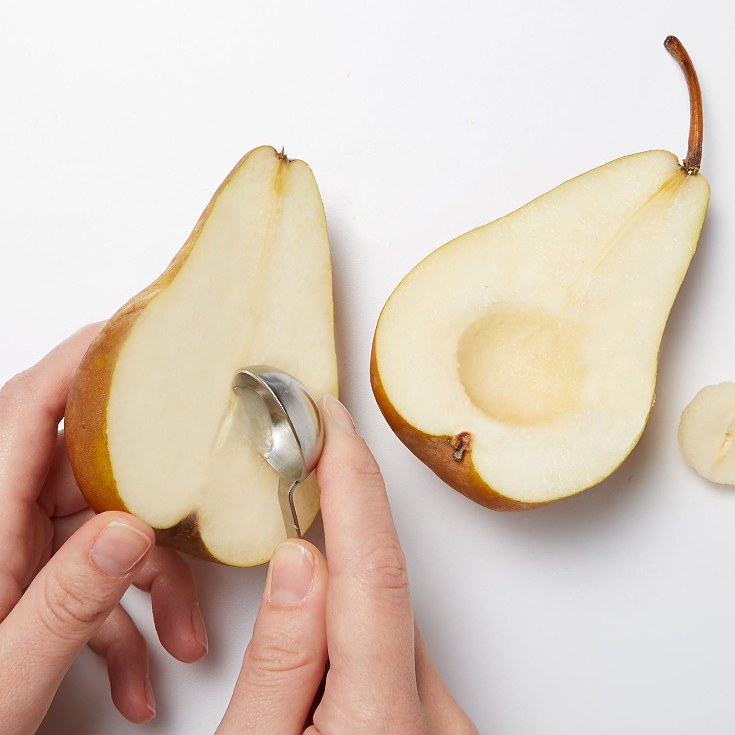 Scooping pear with teaspoon