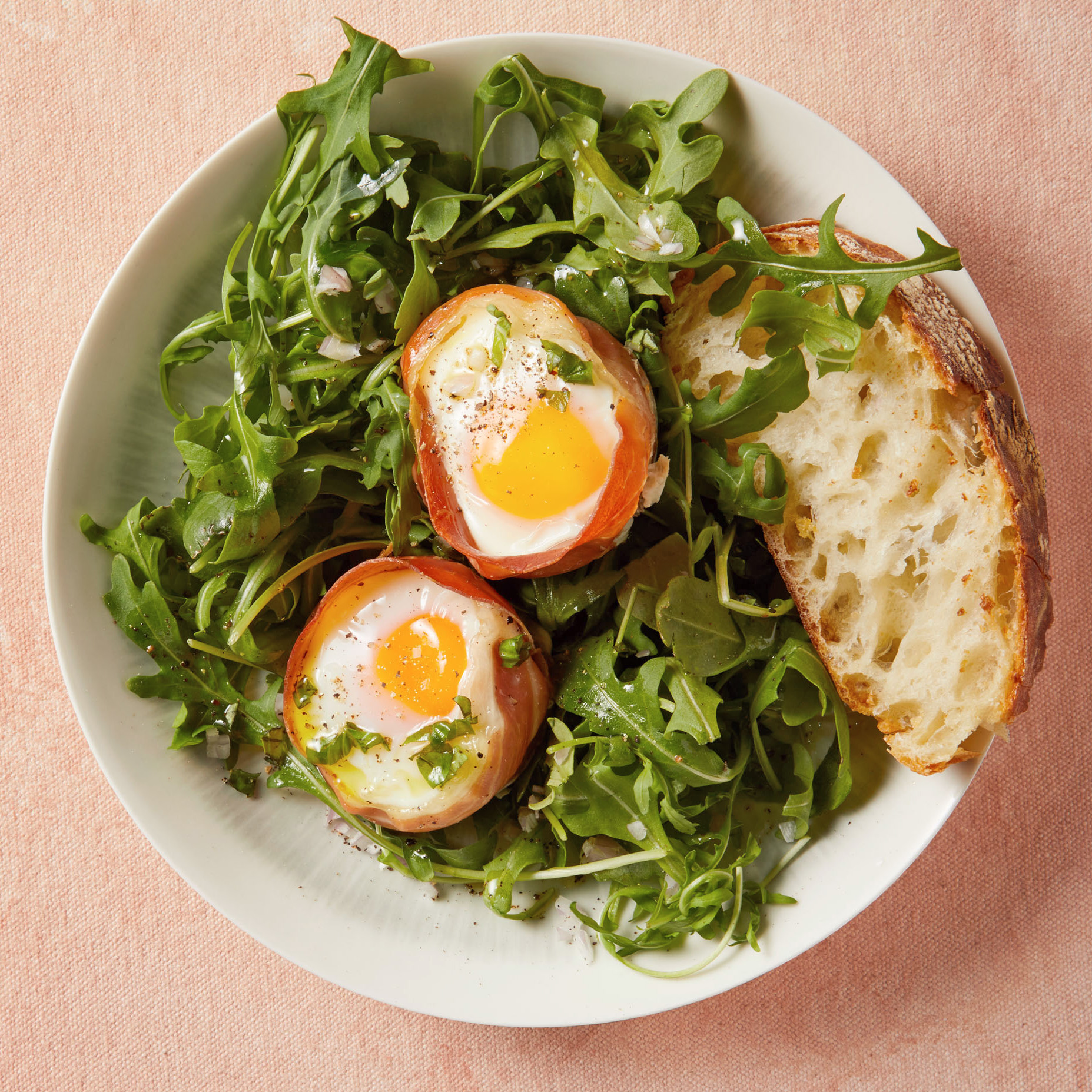 prosciutto-wrapped baked eggs on arugula