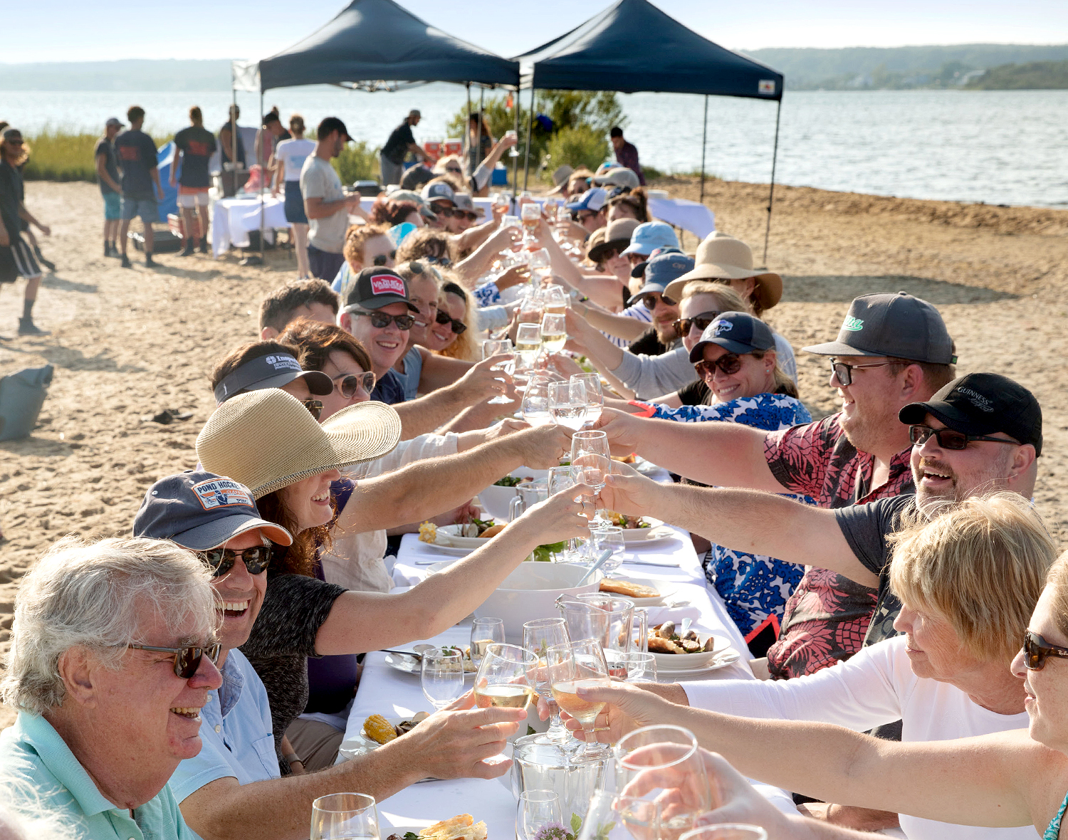 guests raise a toast at oyster dinner