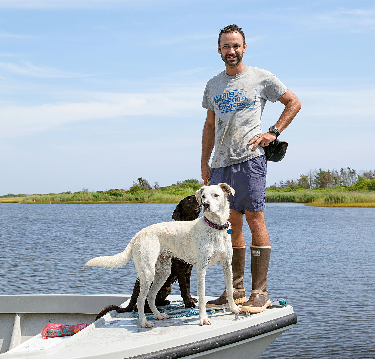 owner of oyster company on boat with dogs