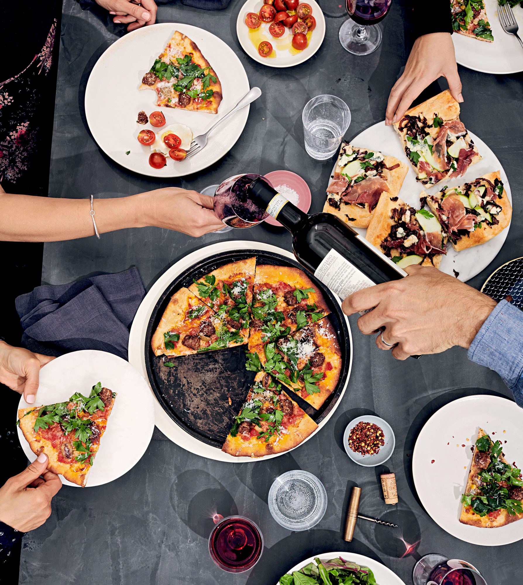 italian dinner table with pizza and wine